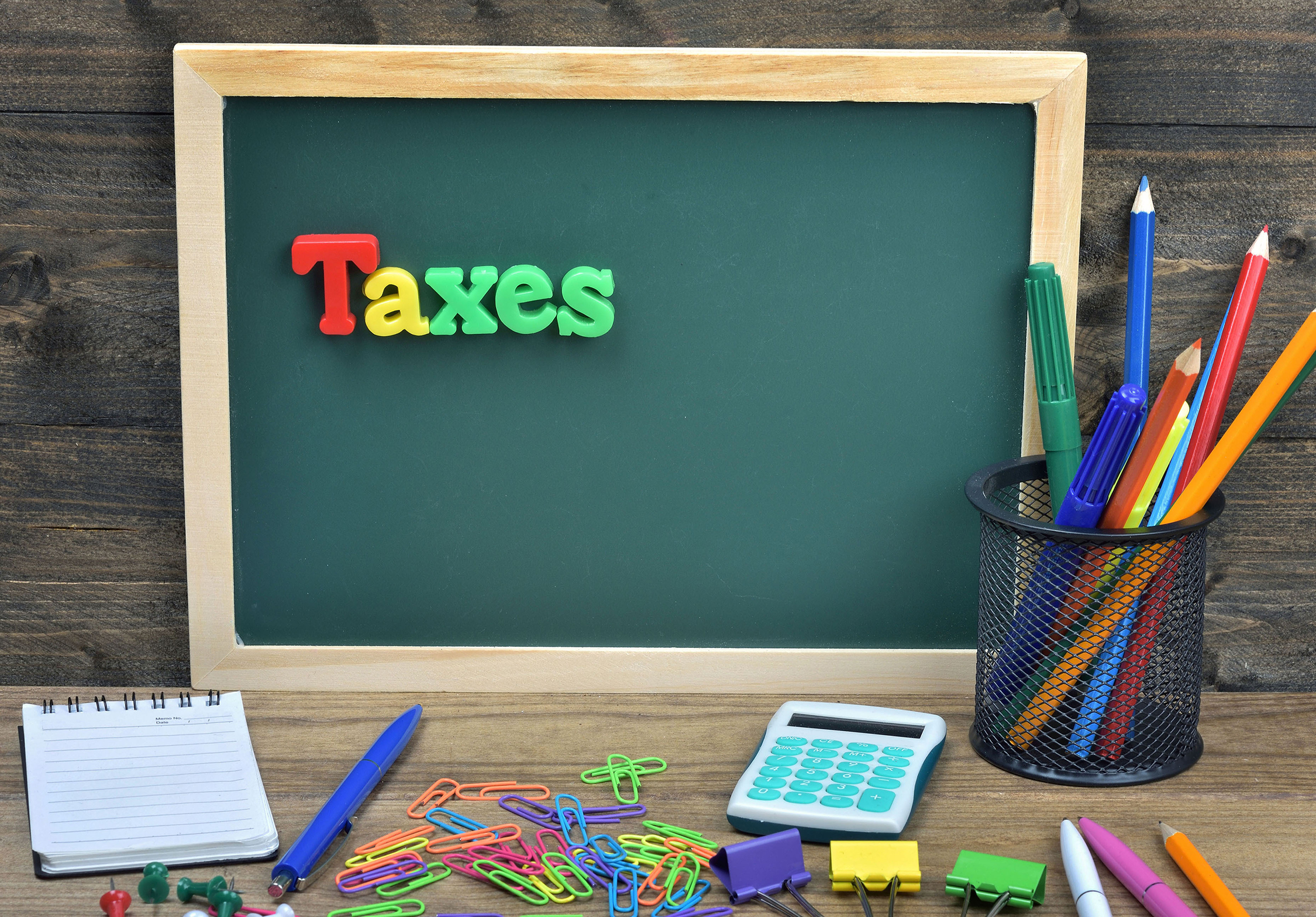 """""""Taxes"""" spelled out in magnets on chalkboard, school setting"""