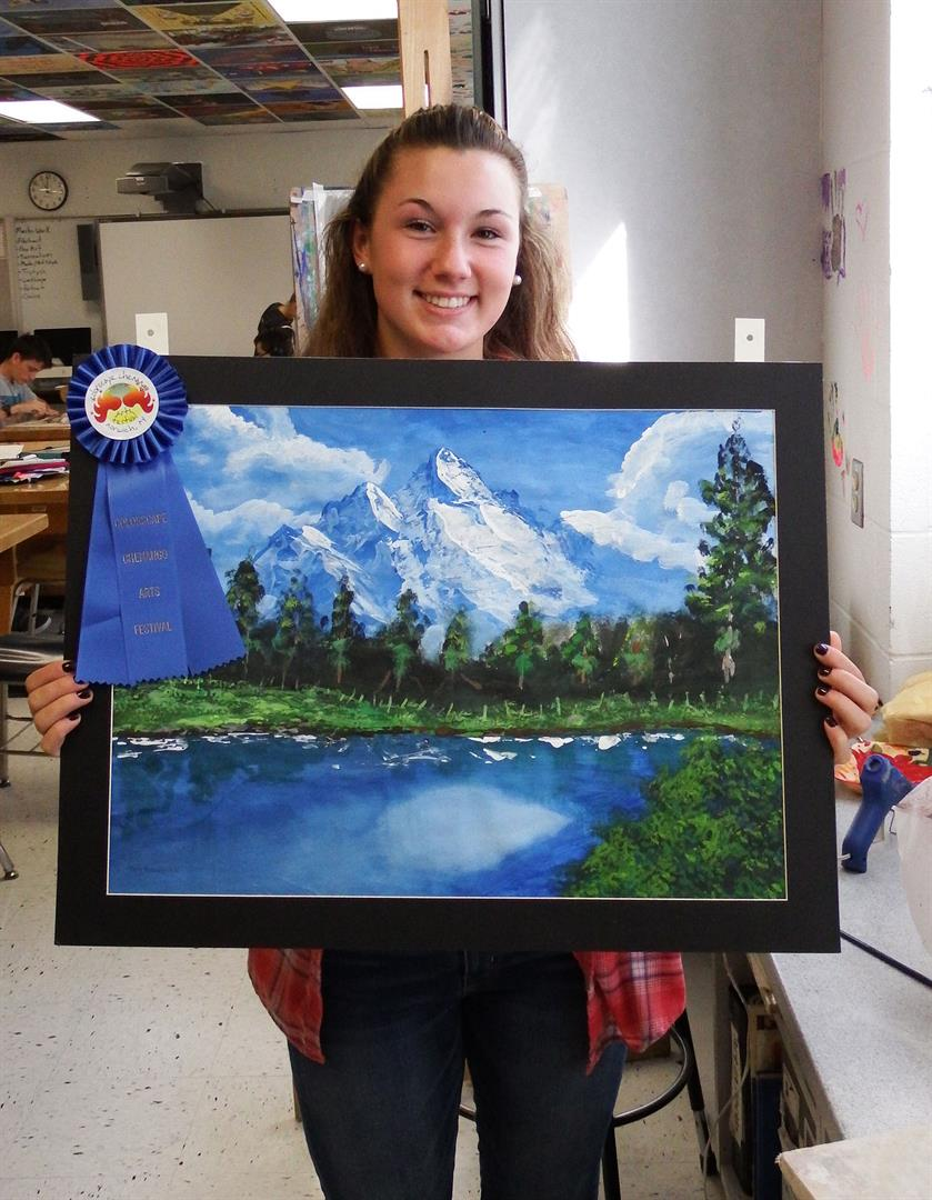 Image of student with prize-winning landscape painting.