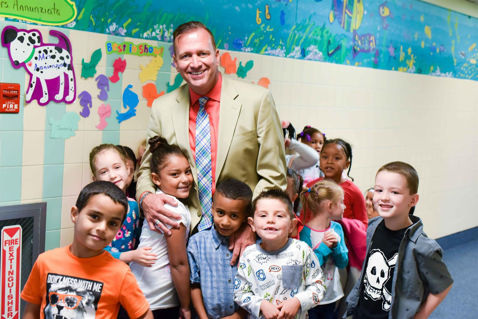 Principal surrounded by kids in hallway