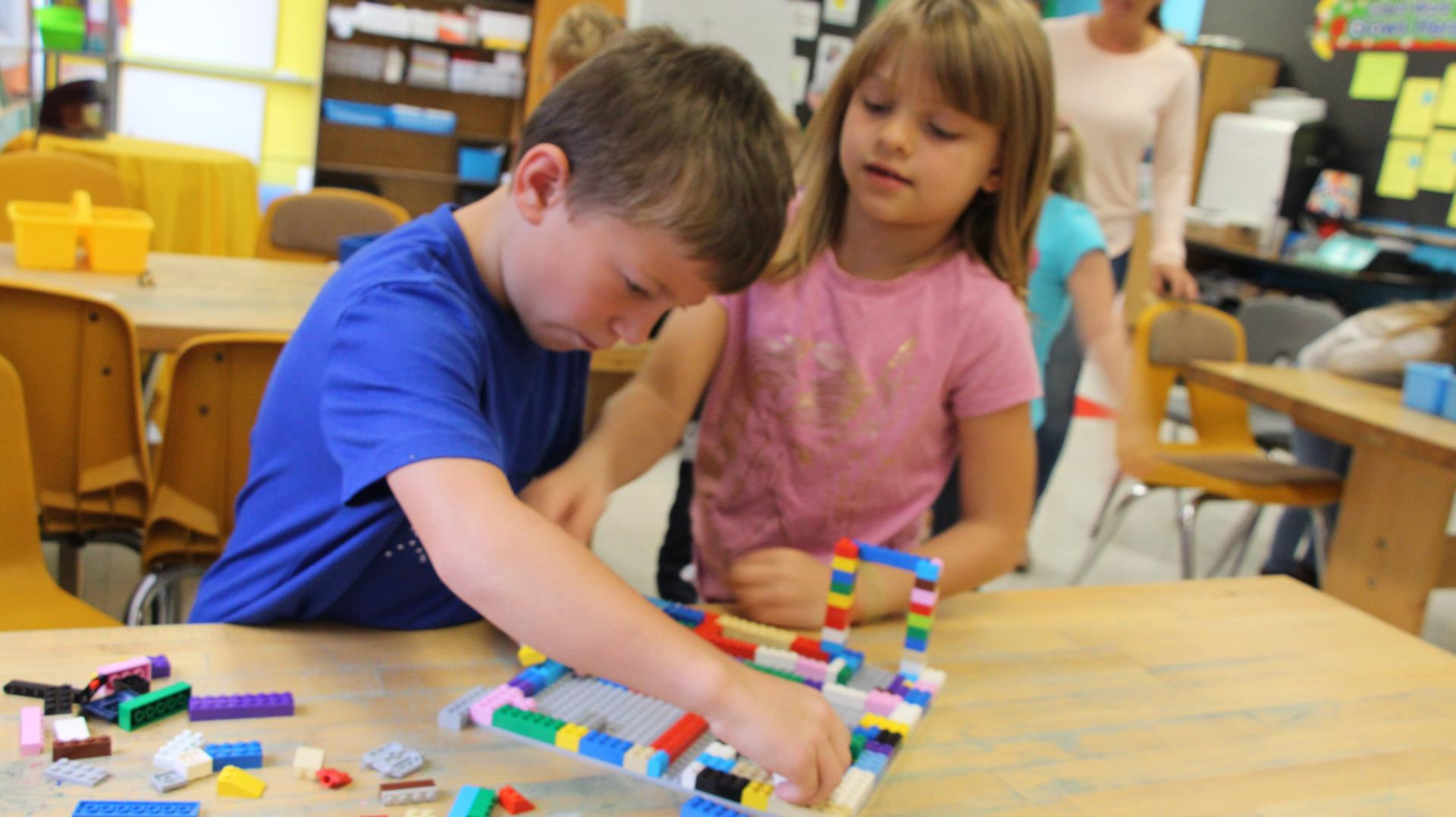A young boy and young girl playing with lego blocks