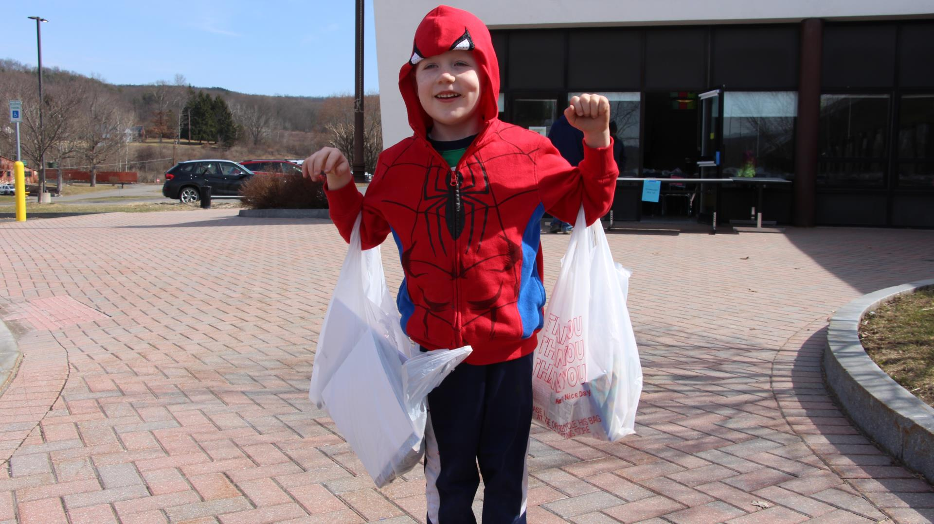 A young boy in a spiderman costume holding two bags