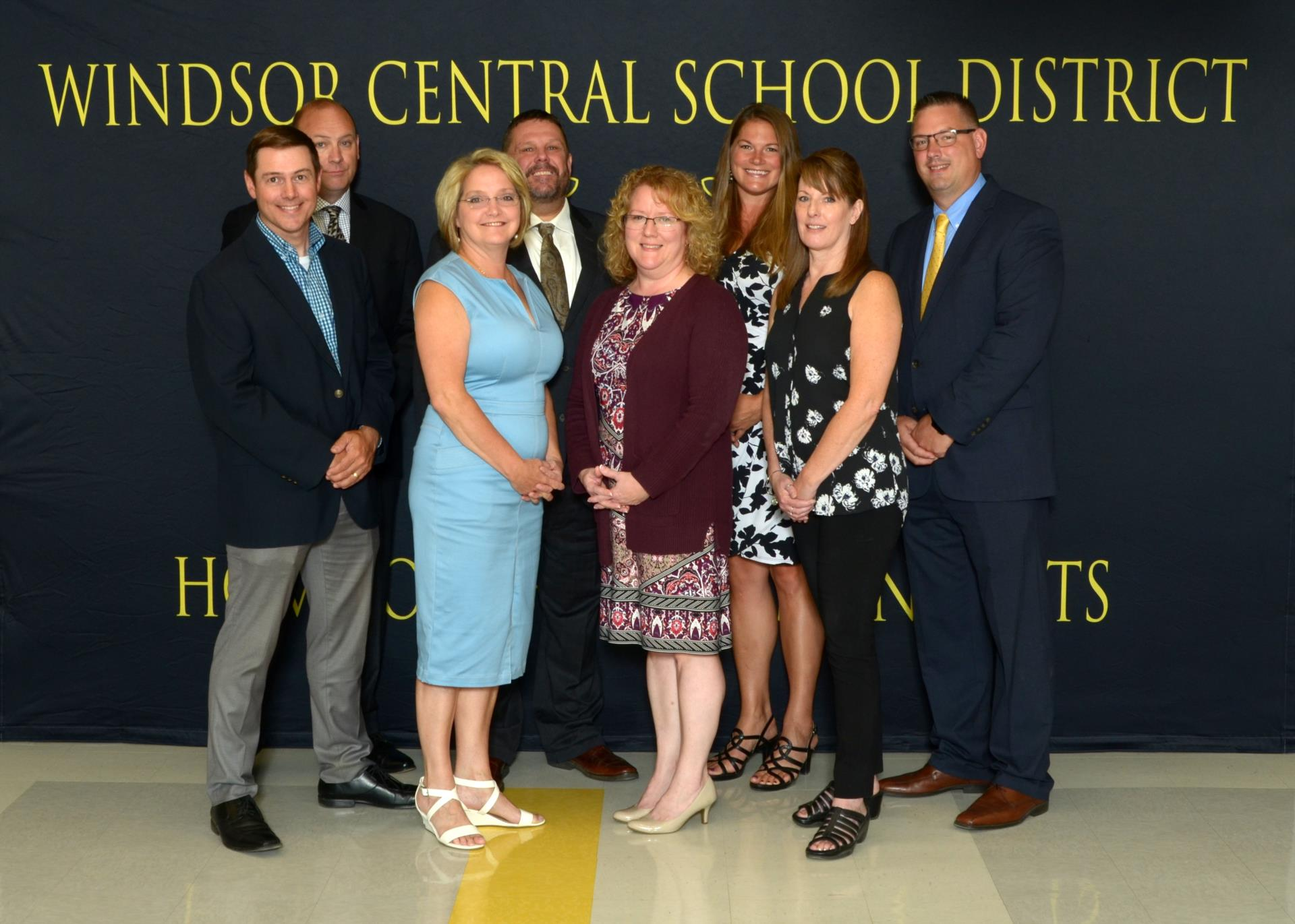 Eight adults standing in front of a Windsor Central School District Sign