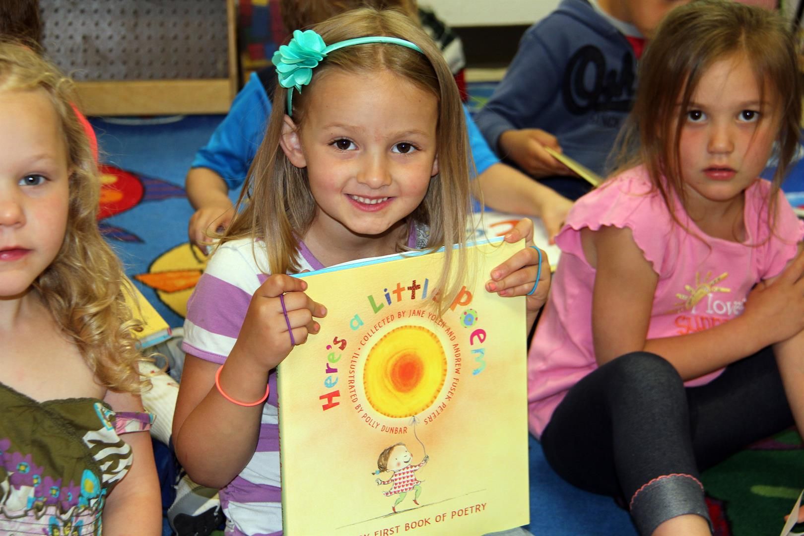 girls smiling holding book