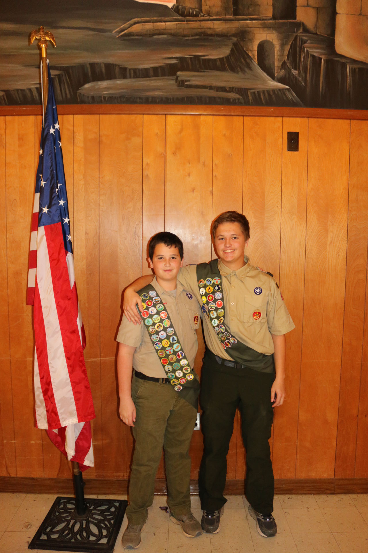 Two boy scouts stand with flag