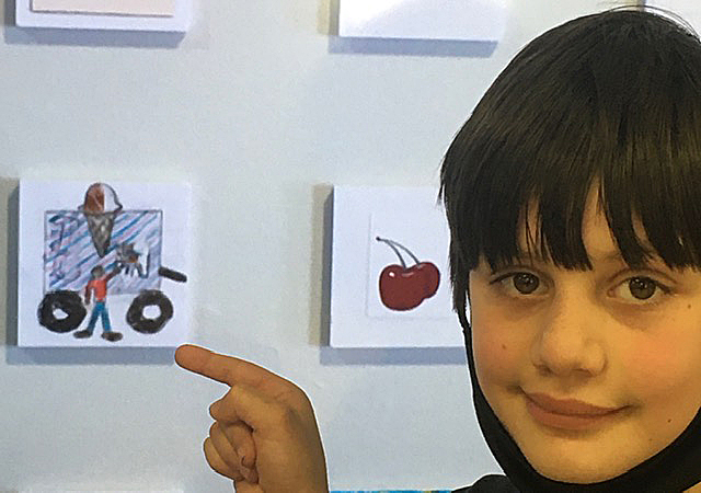 Student points to his artwork.