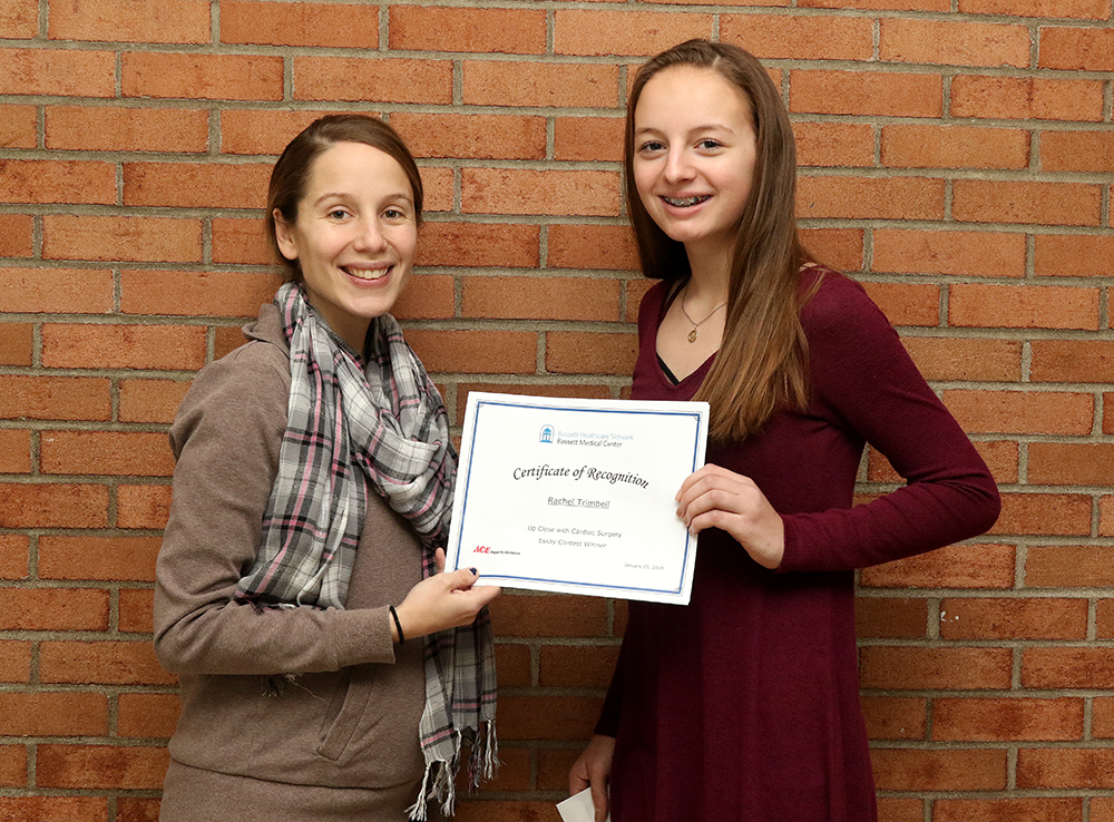 Teacher Megan Loomis presents a certificate to Rachel Trimbell