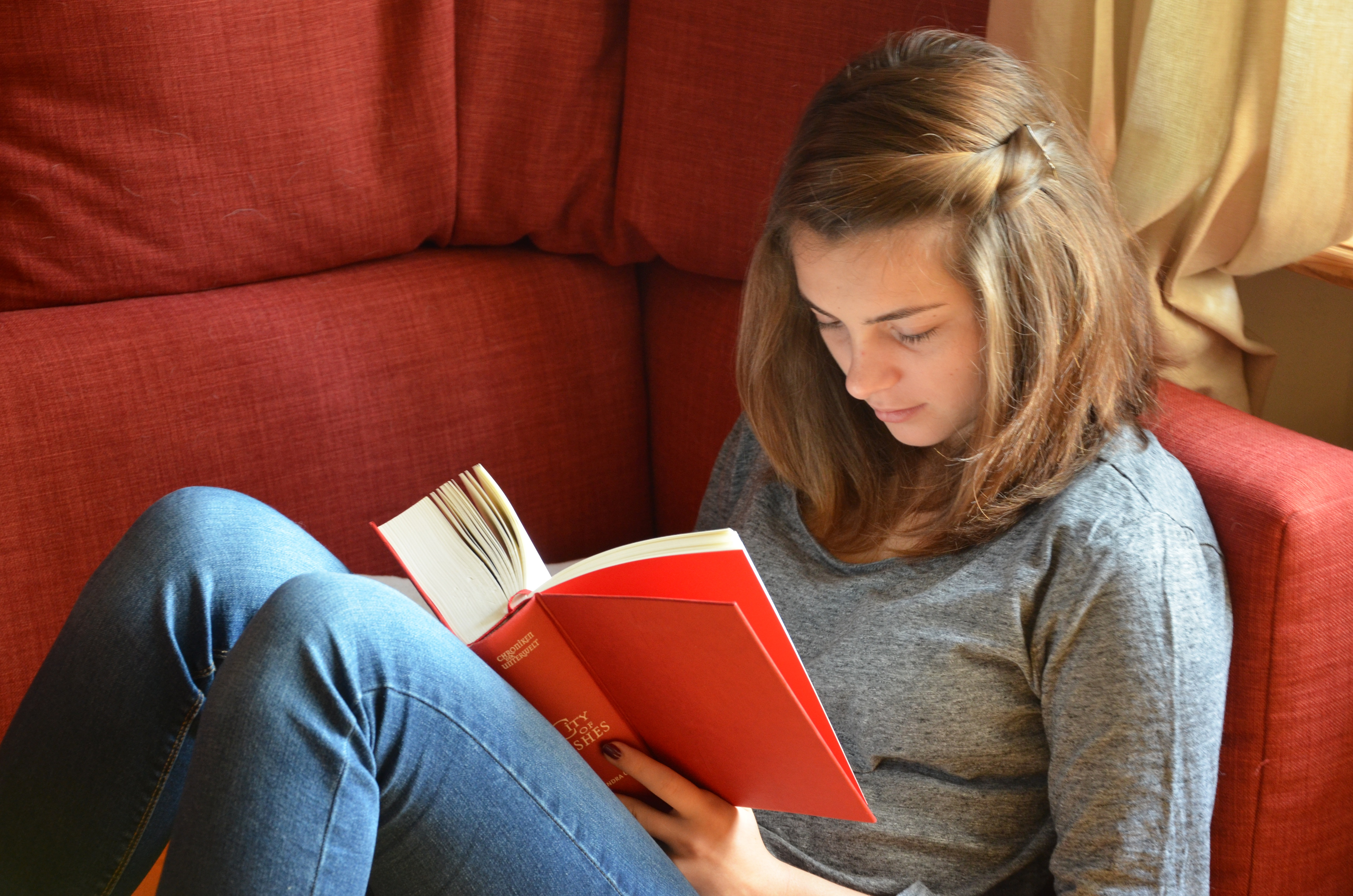 Young woman reading book a couch