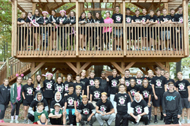 The entire Vestal High School Varsity and Junior Varsity soccer teams and some Modified Soccer teammates pose for a group photo on and under a wooden structure at Binghamton's Recreation Park before beginning the Making Strides for Breast Cancer Walk in October 2017.