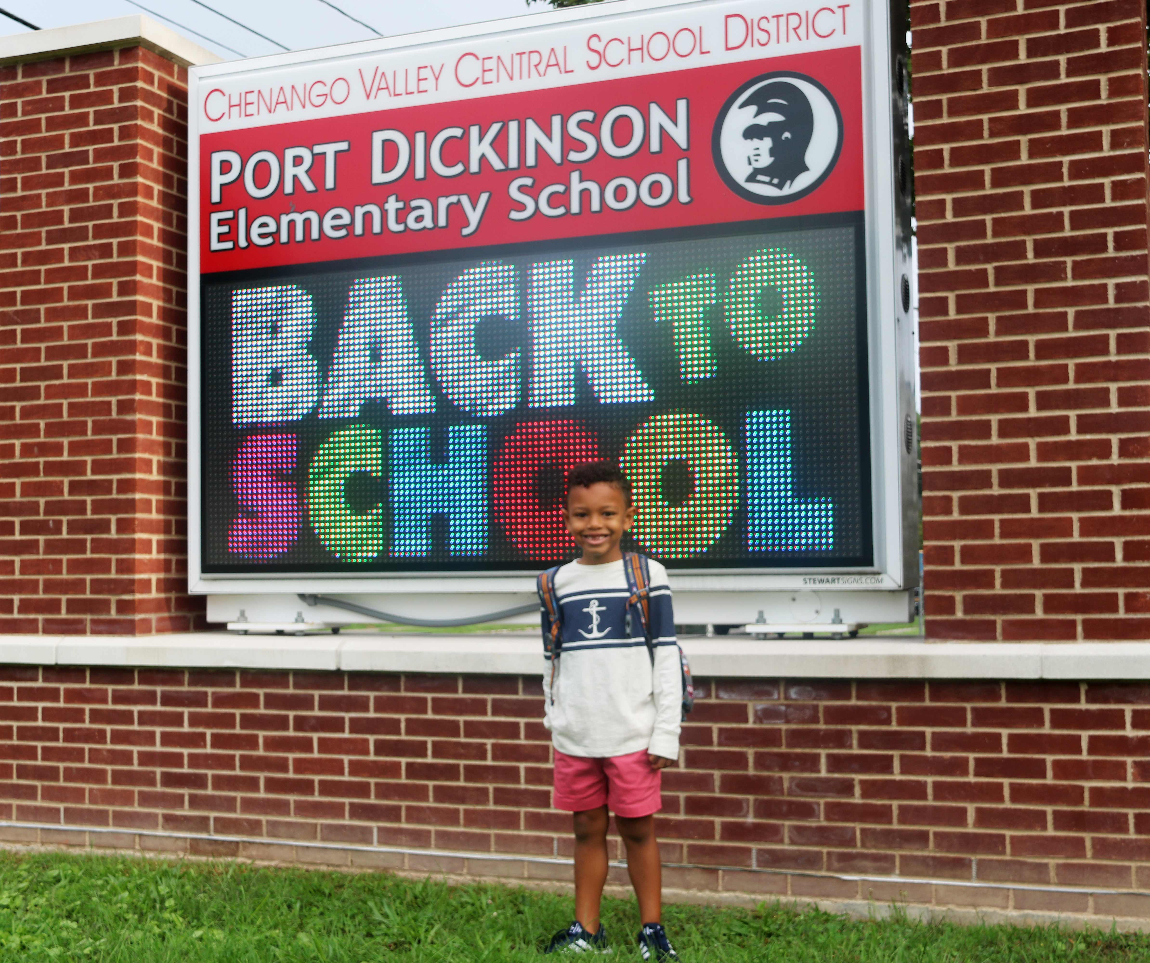 student standing next to back to school marquee