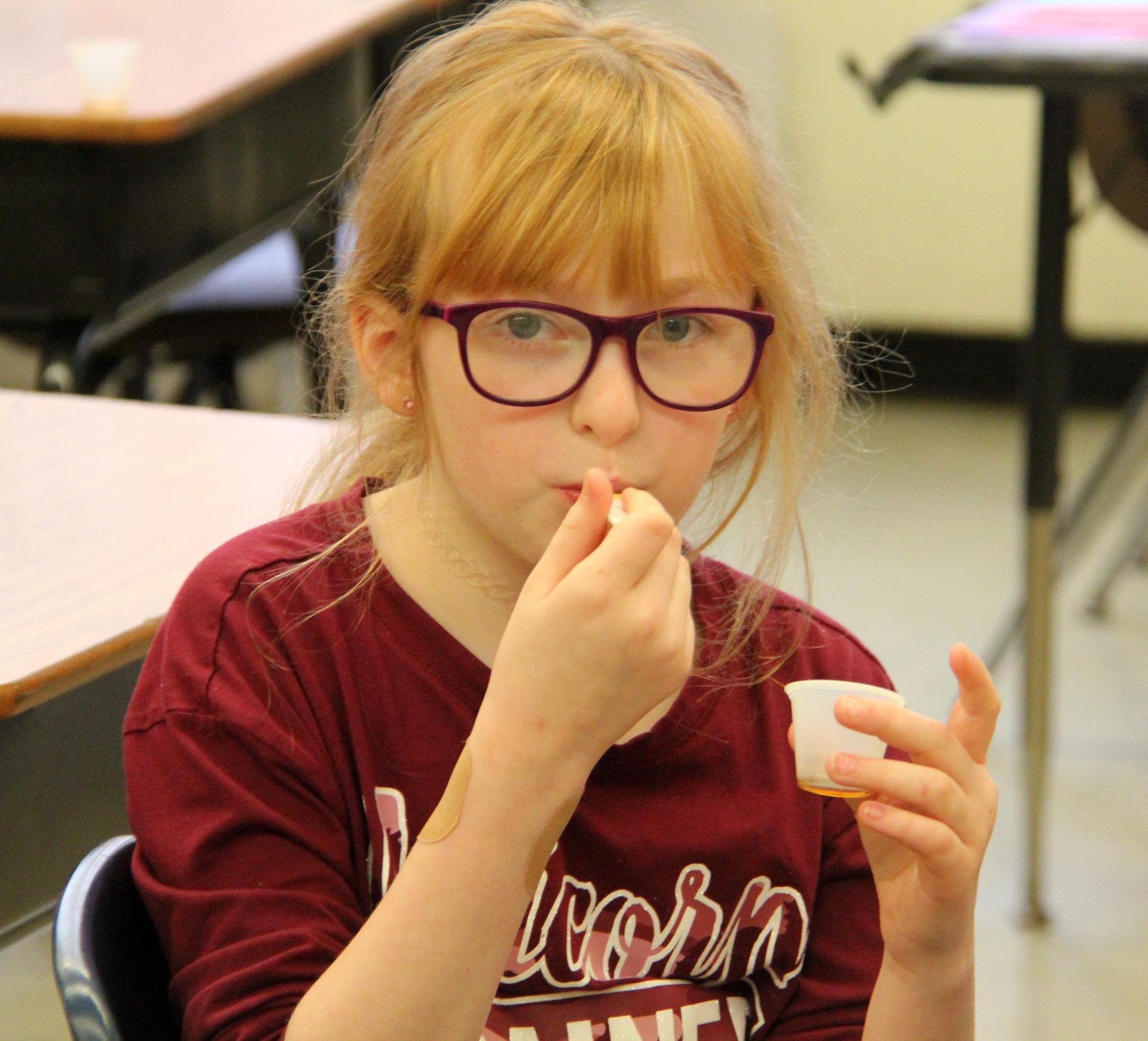 student taste testing maple cream
