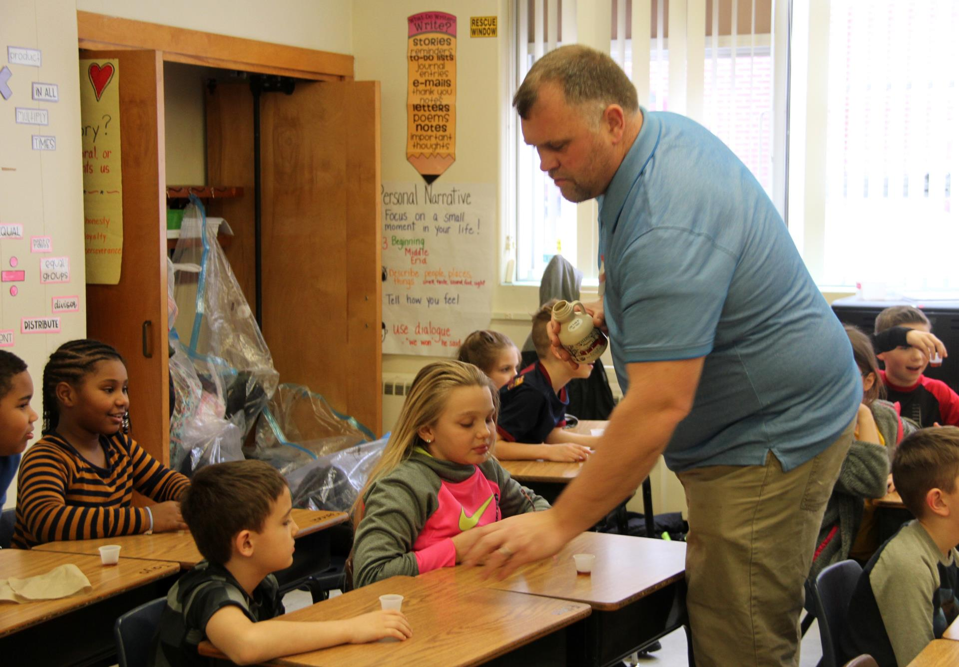 program educator giving students maple syrup