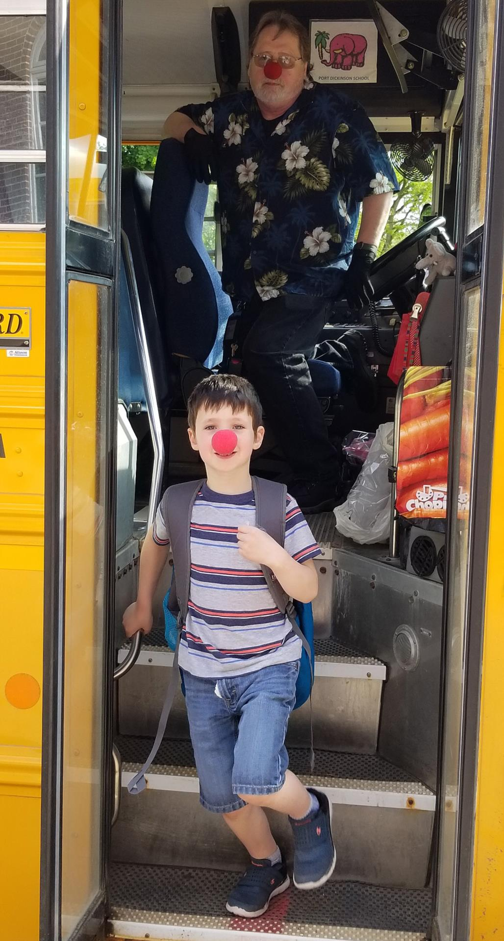 student exiting school bus wearing red nose