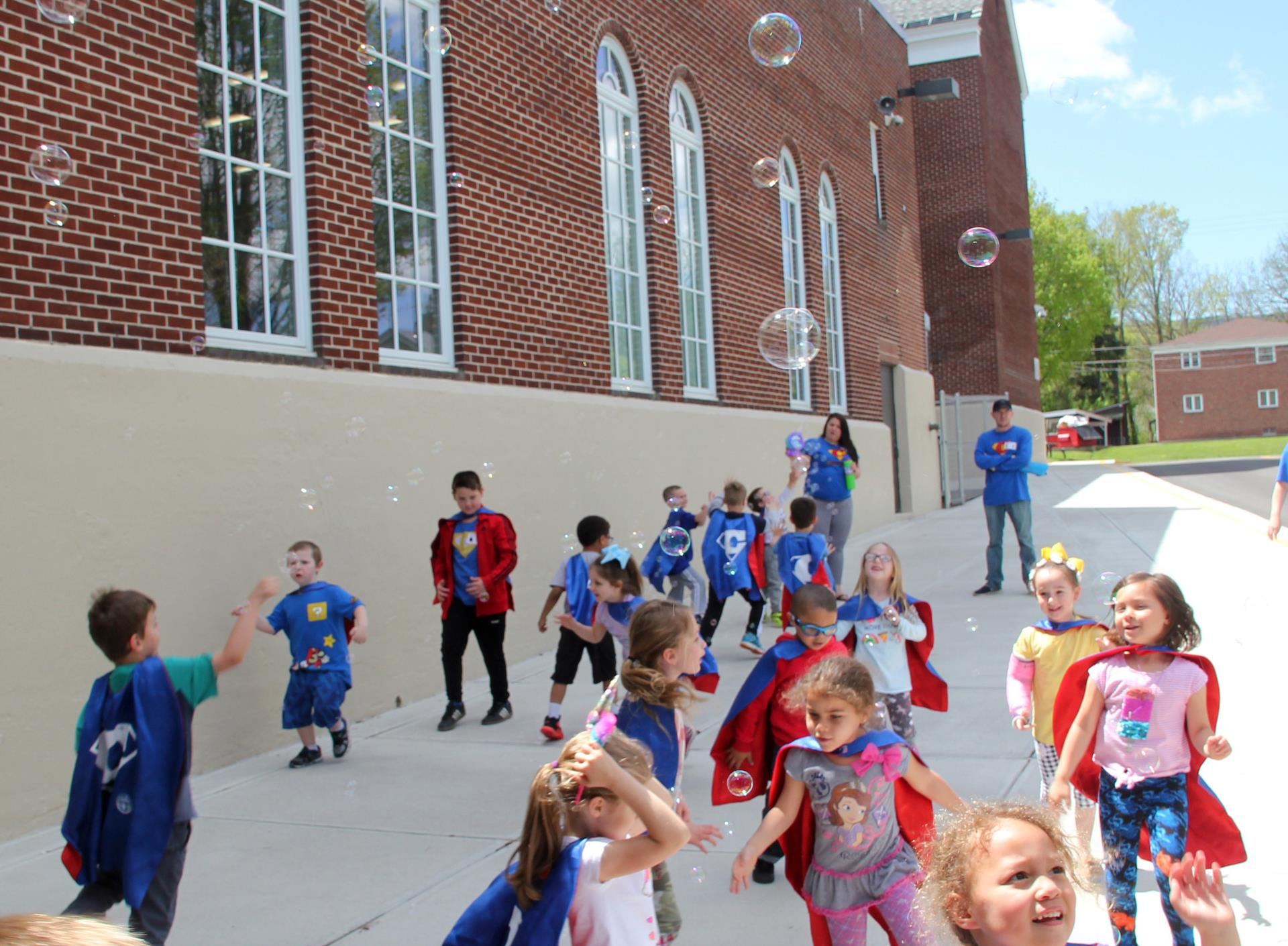 students playing in bubbles