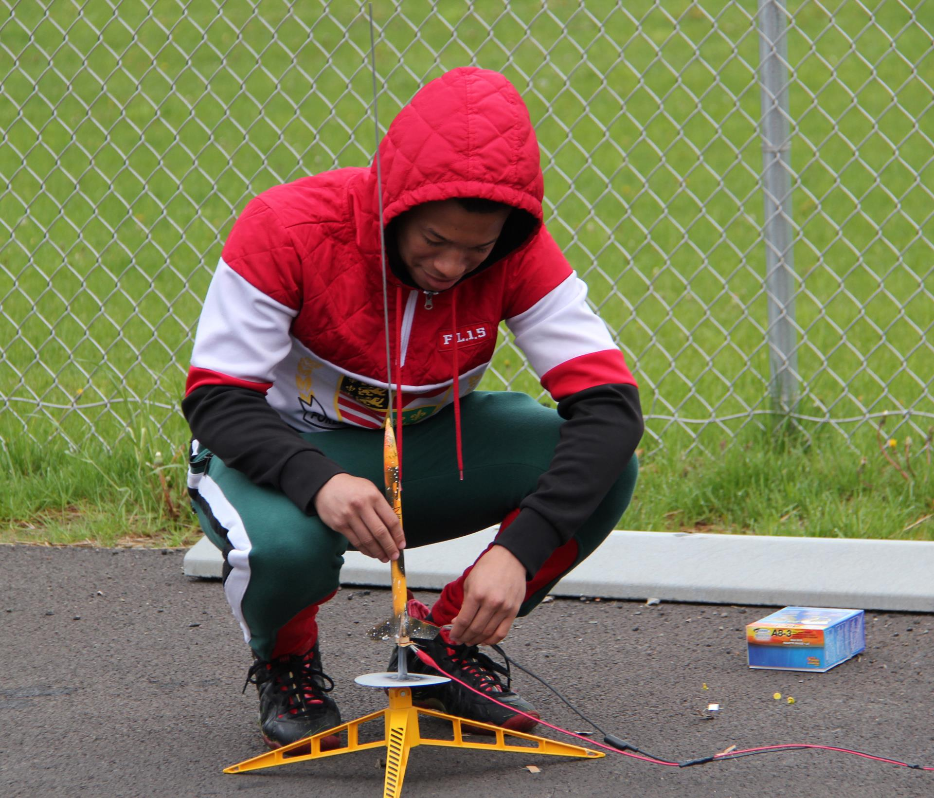 student putting model rocket onto launch pad