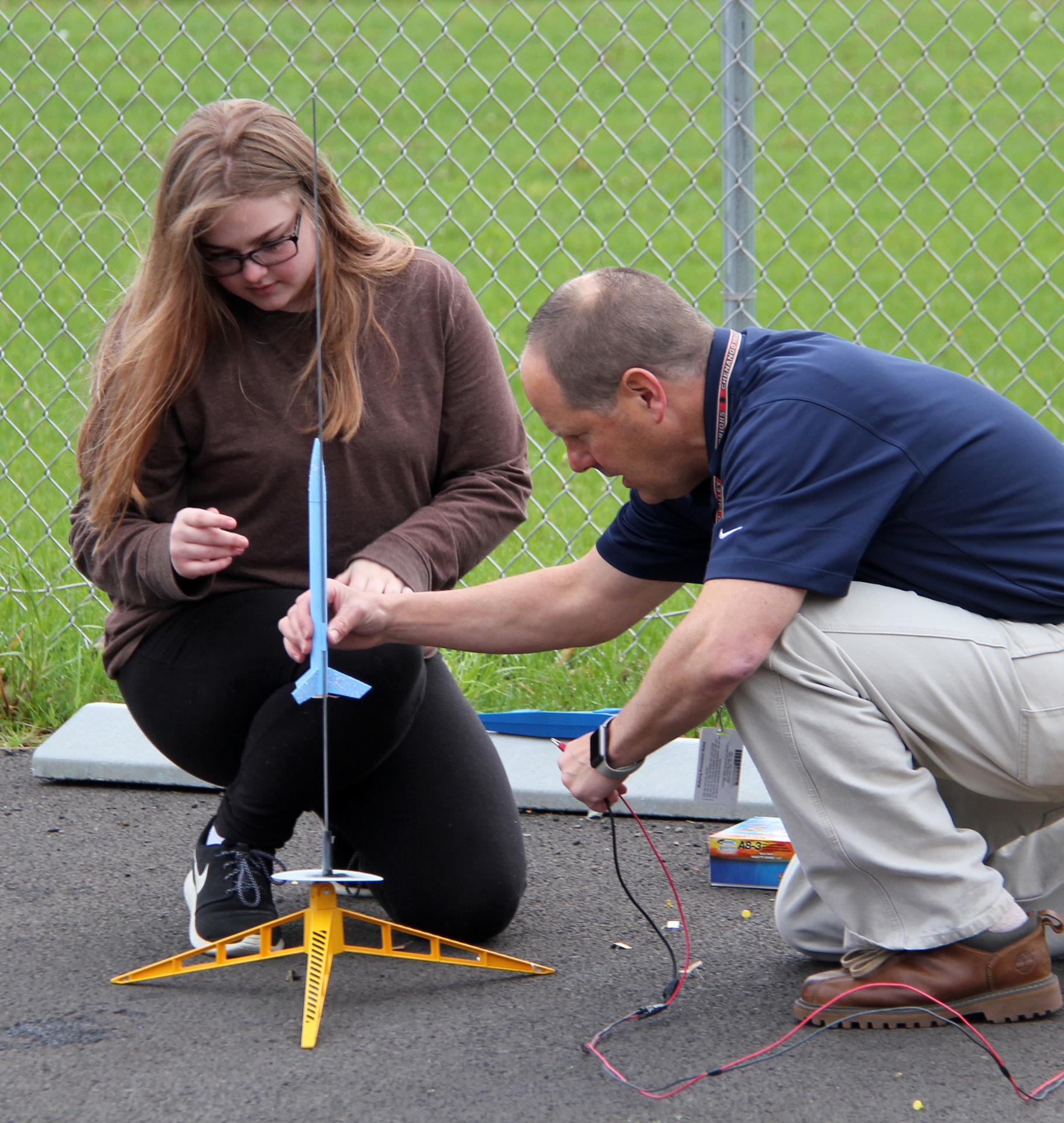 student and teacher putting model rocket onto launch pad