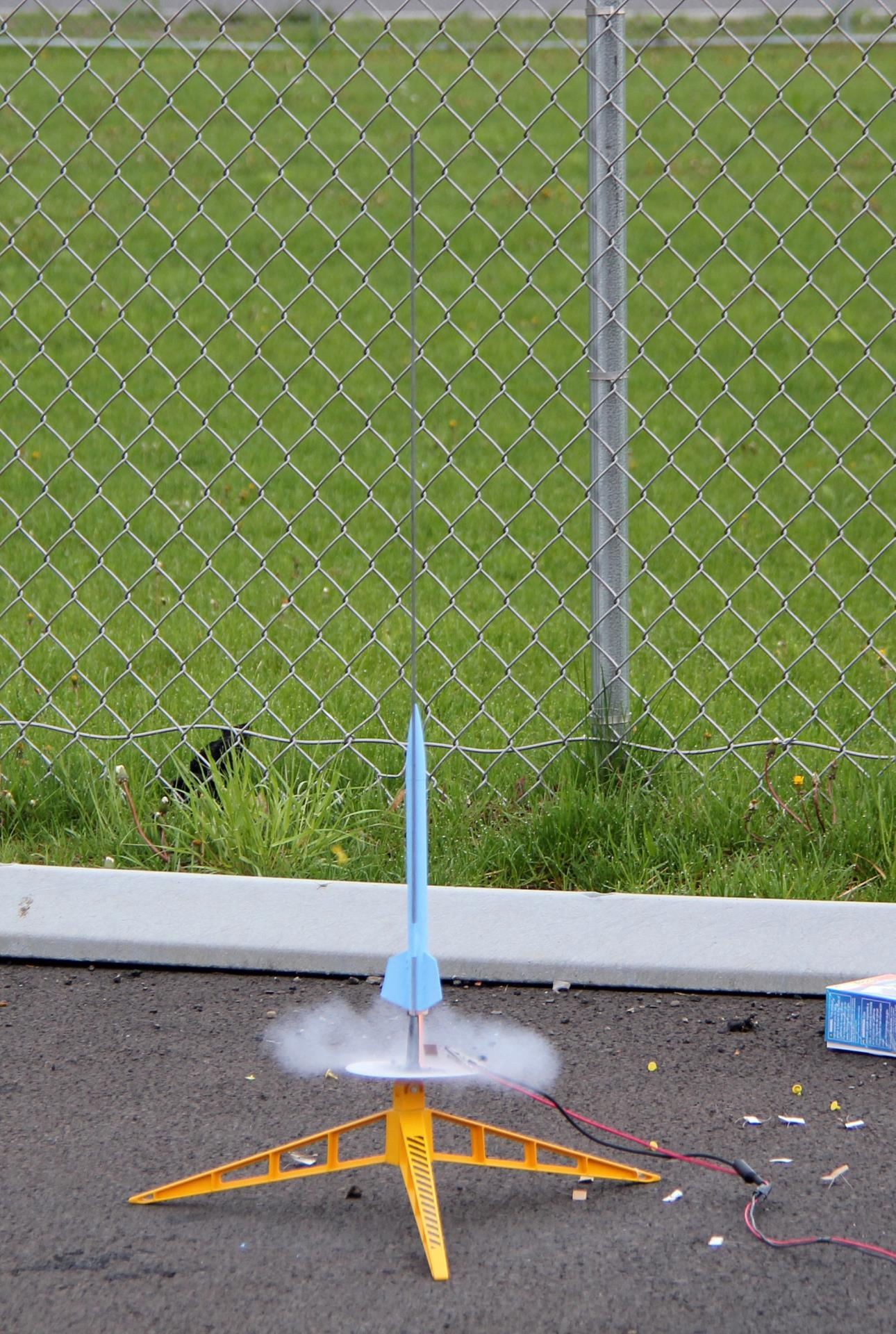 blue model rocket beginning to lift off from launch pad