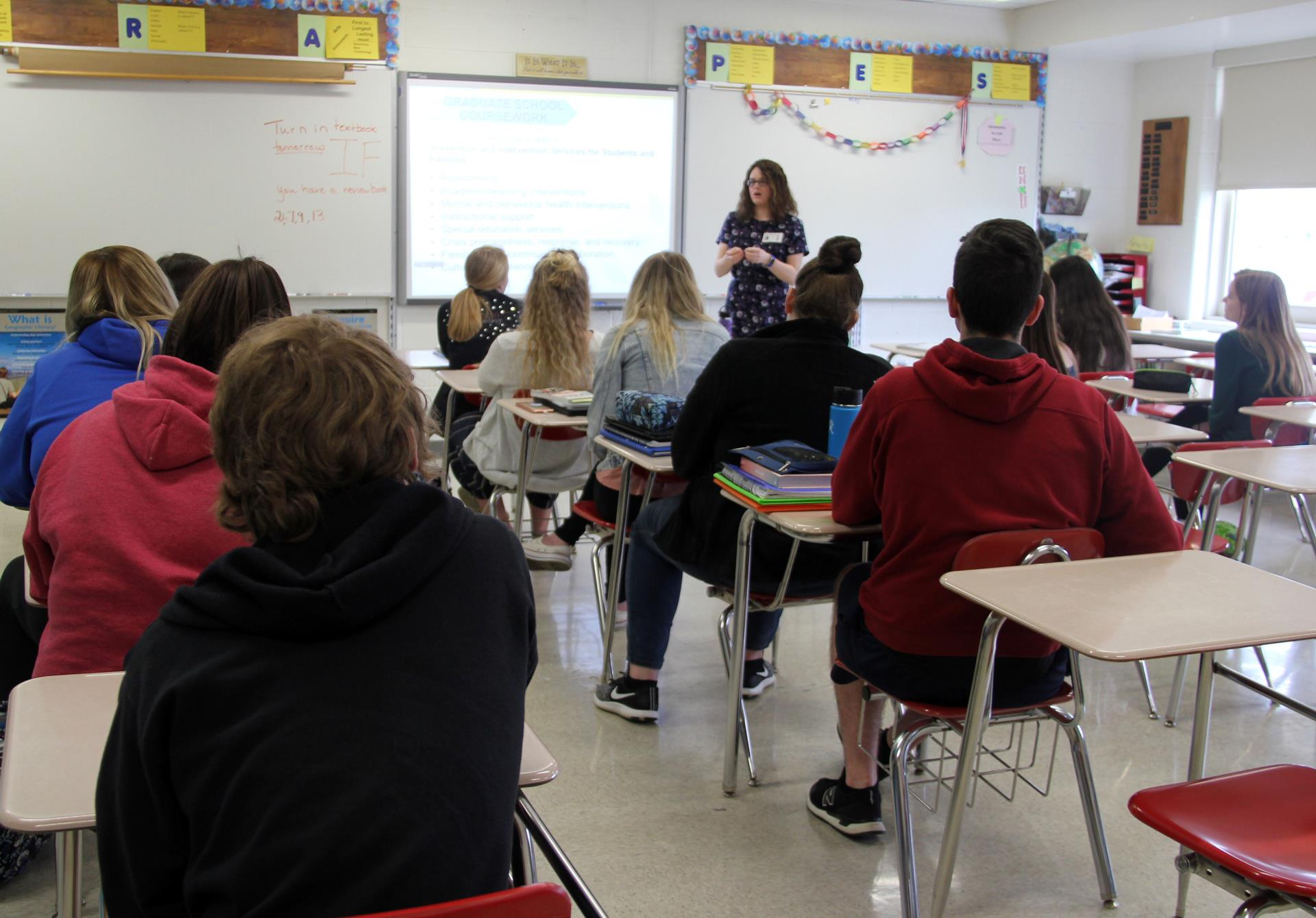 wide shot of school psychologist speaking with students