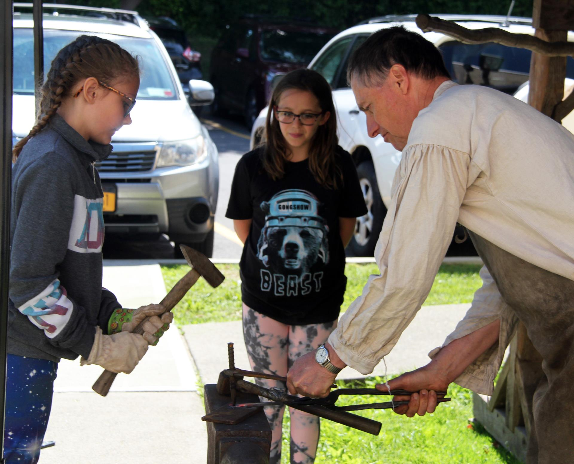 medium shot of students working with fred the blacksmith
