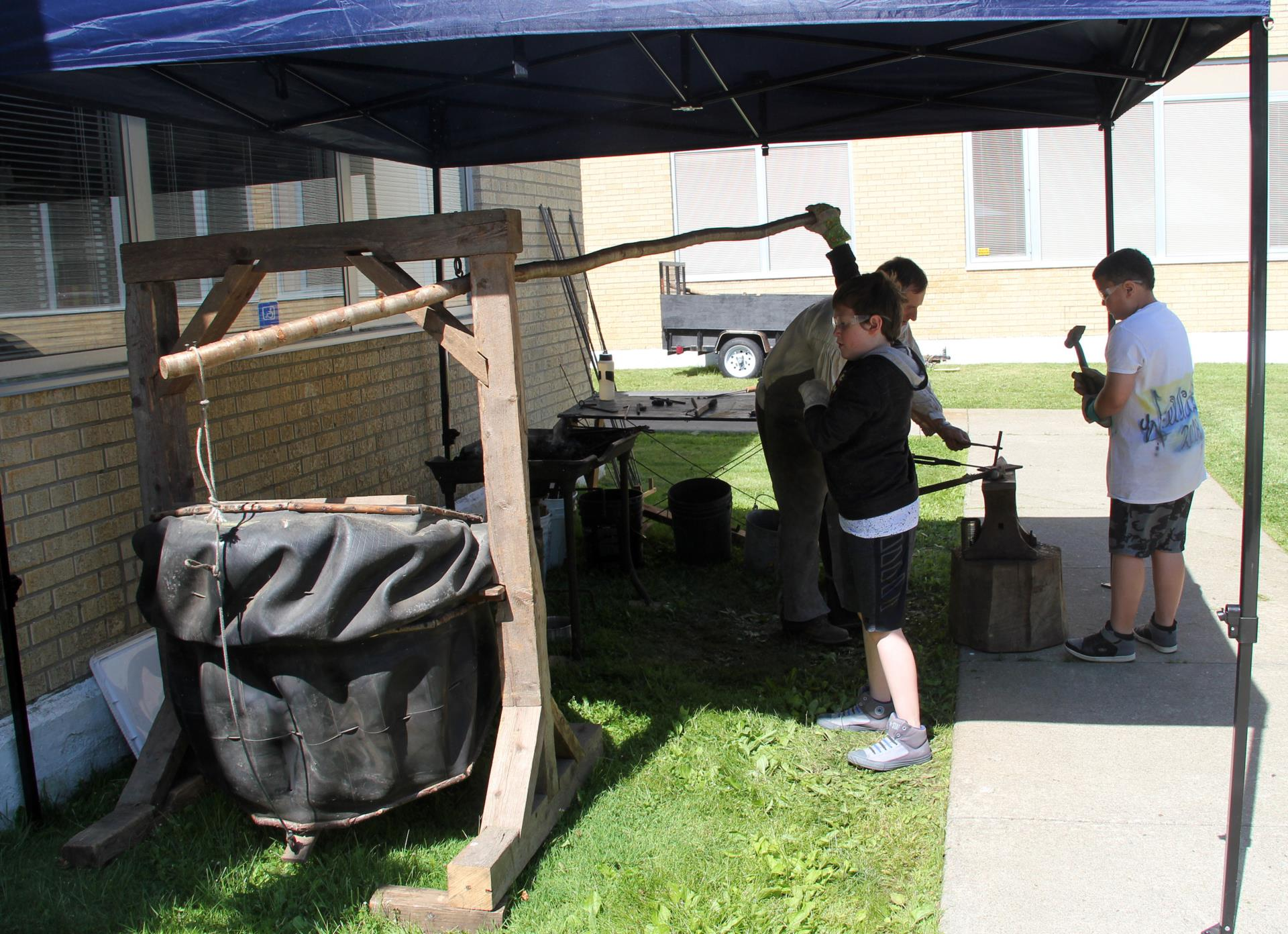 wide shot of students working with fred the blacksmith