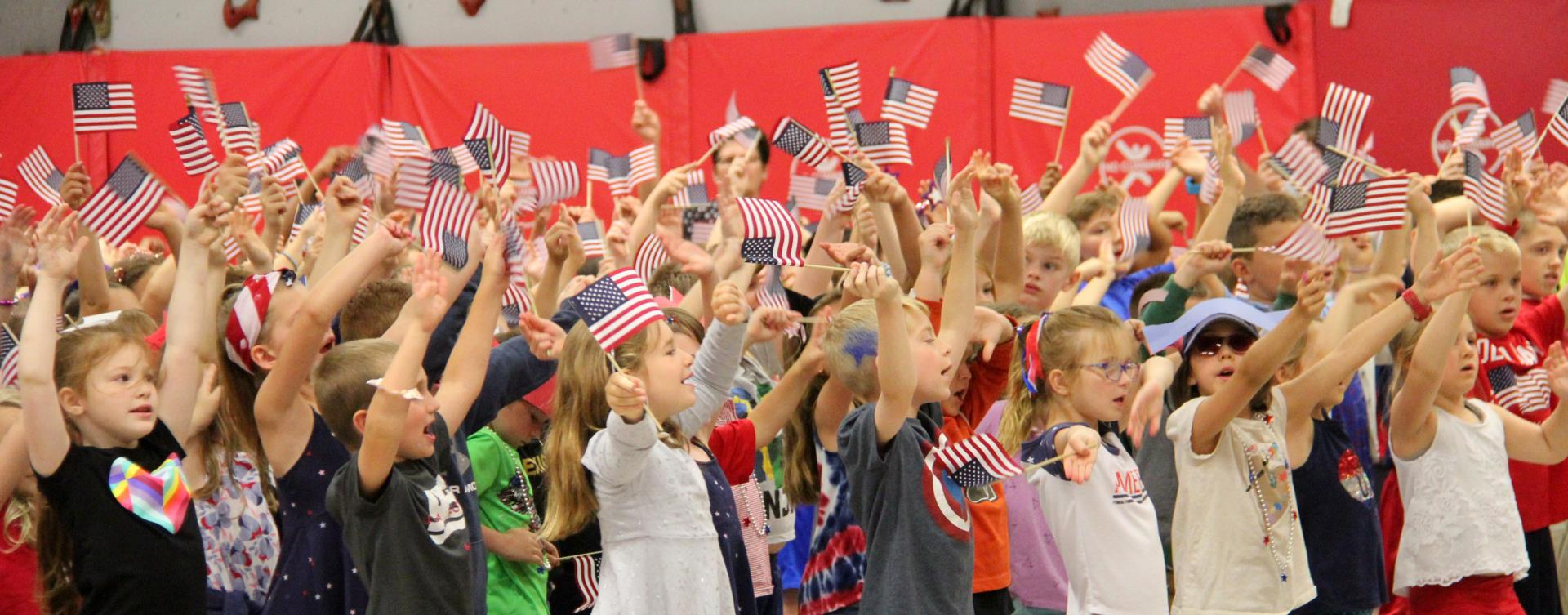 students waving flags in flag day ceremony