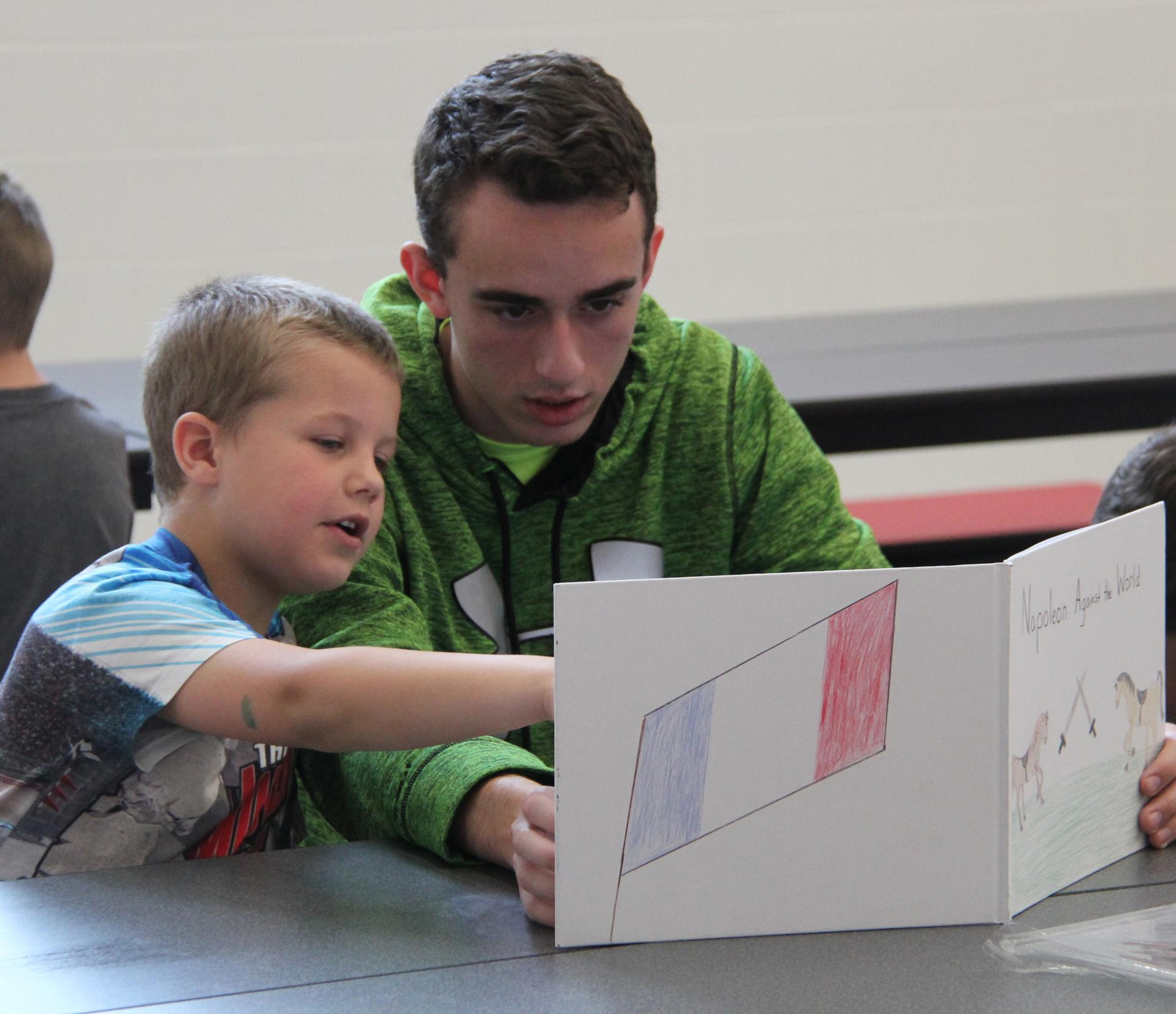 high school student reading to kindergarten student