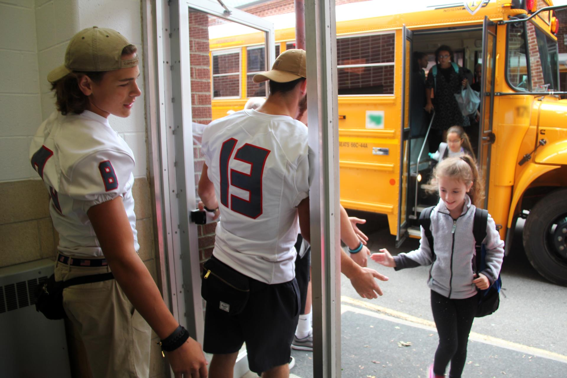 elementary students giving football players high fives