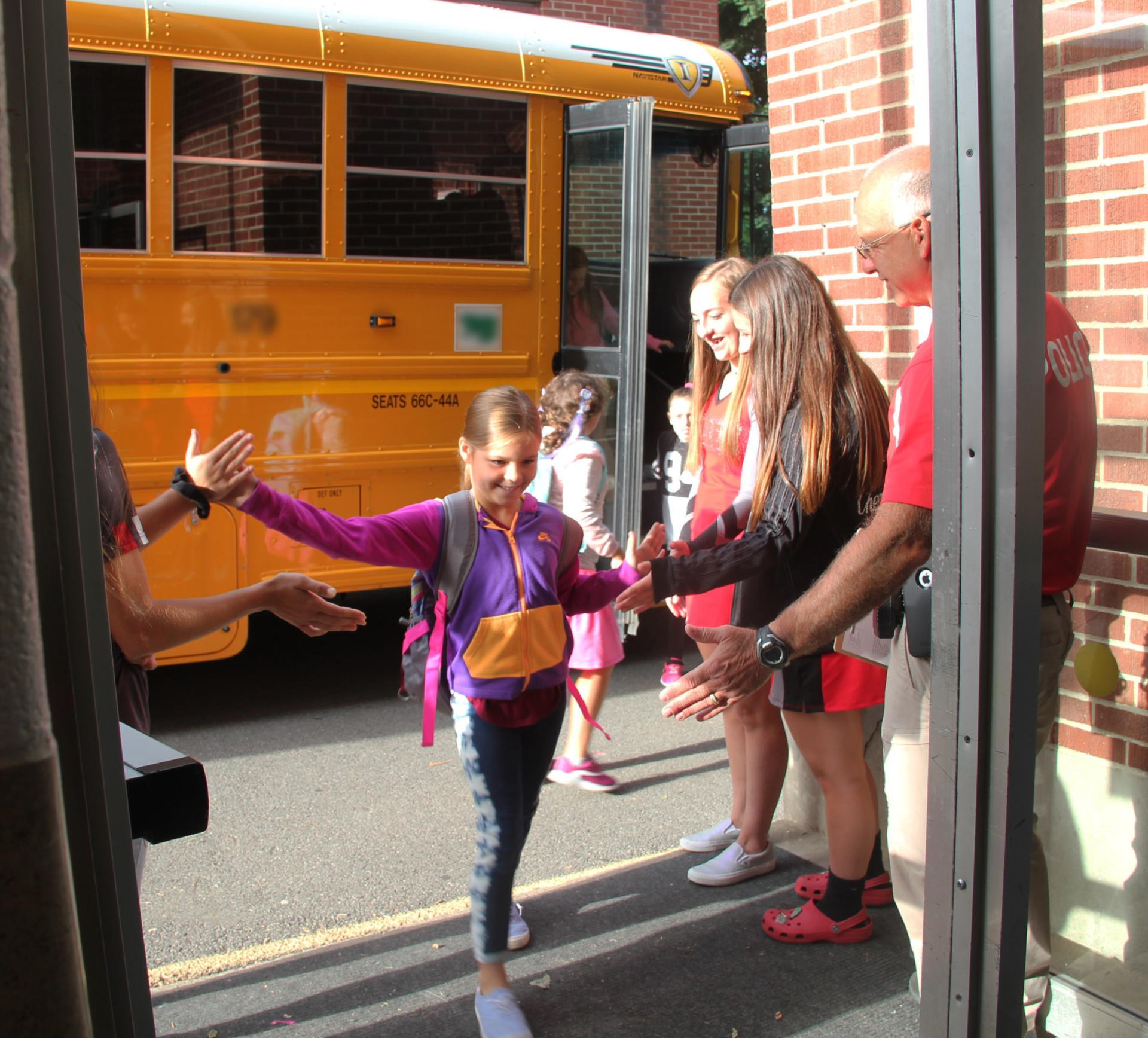 athletes giving chenango bridge elementary students high fives
