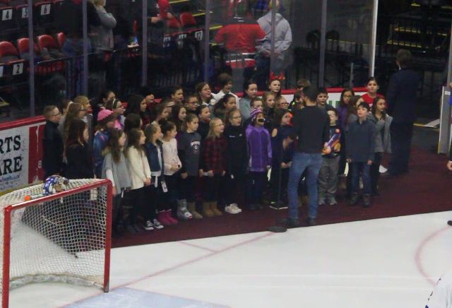 students singing in hockey rink