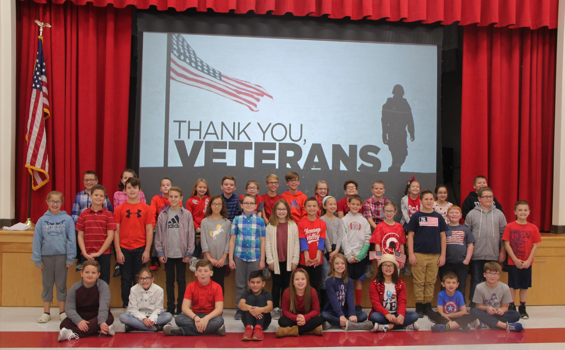 students in front of thank you veterans sign