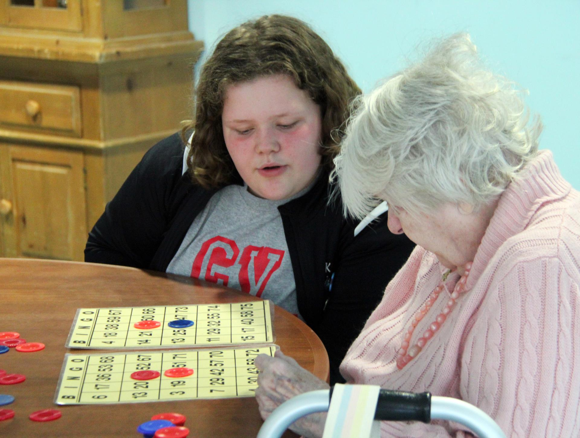 student helping resident with bingo