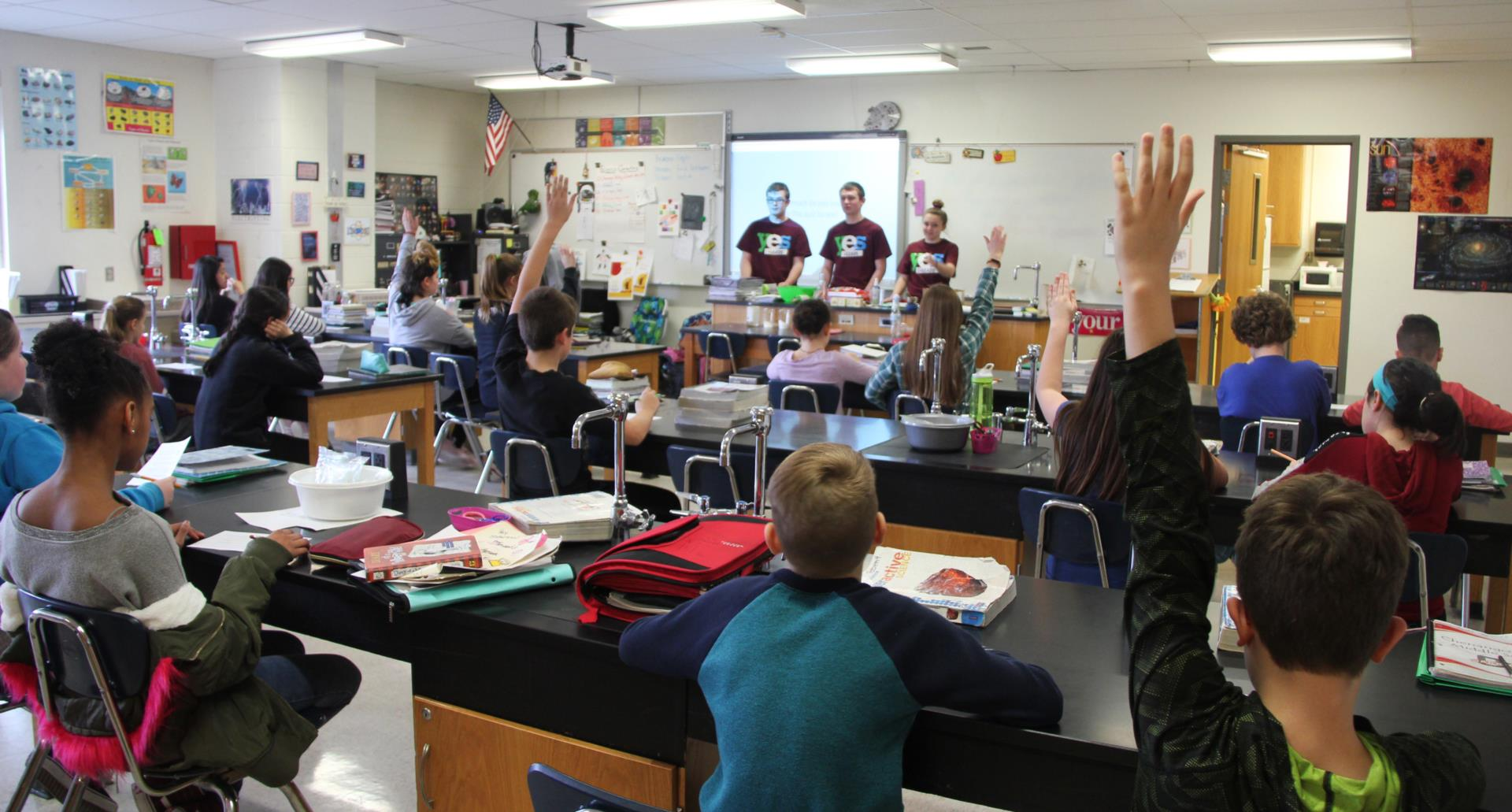 middle school students raising hands during yes leads presentation