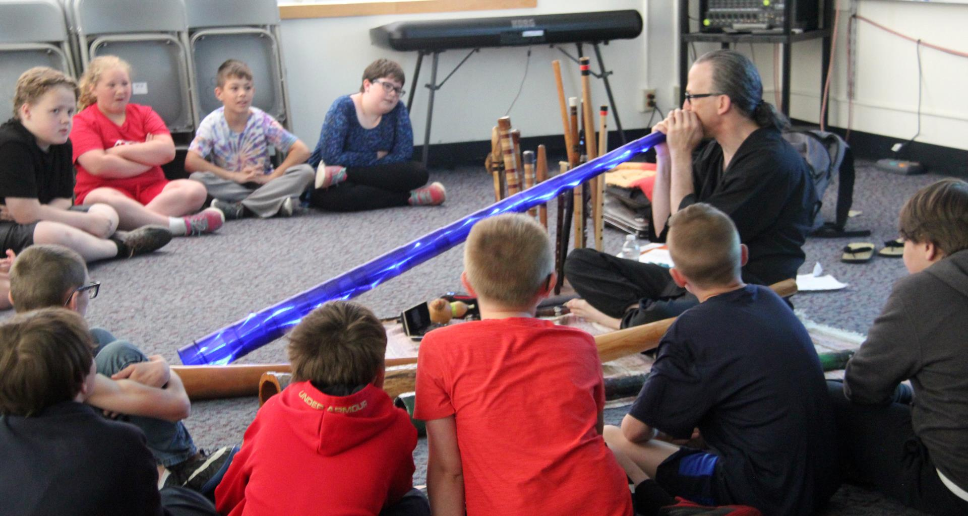 students watching presenter play didgeridoo