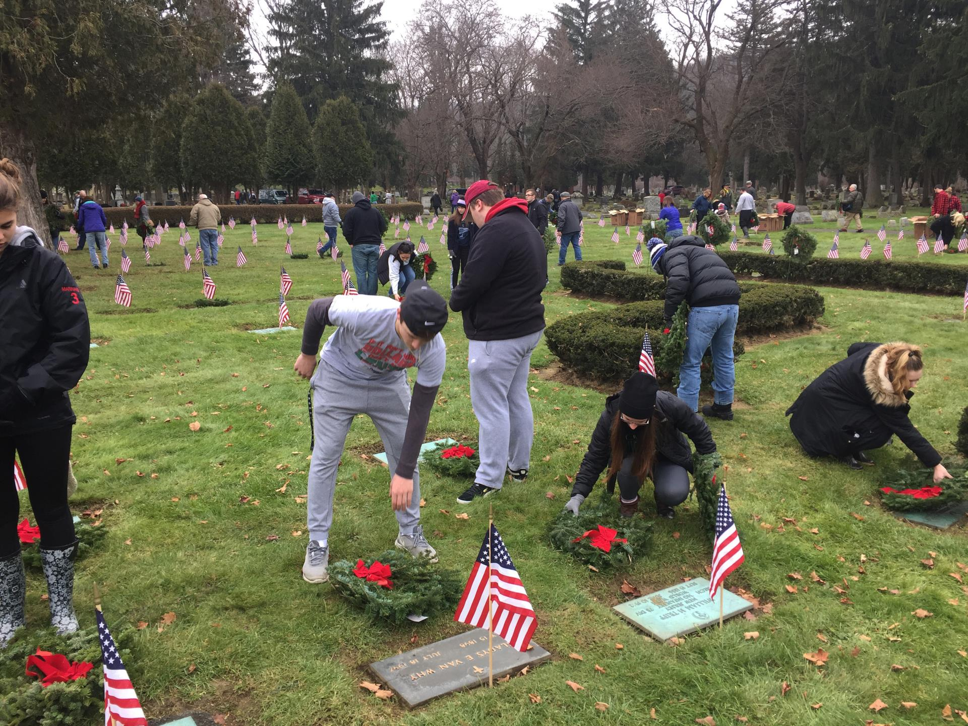 students putting wreaths on graves