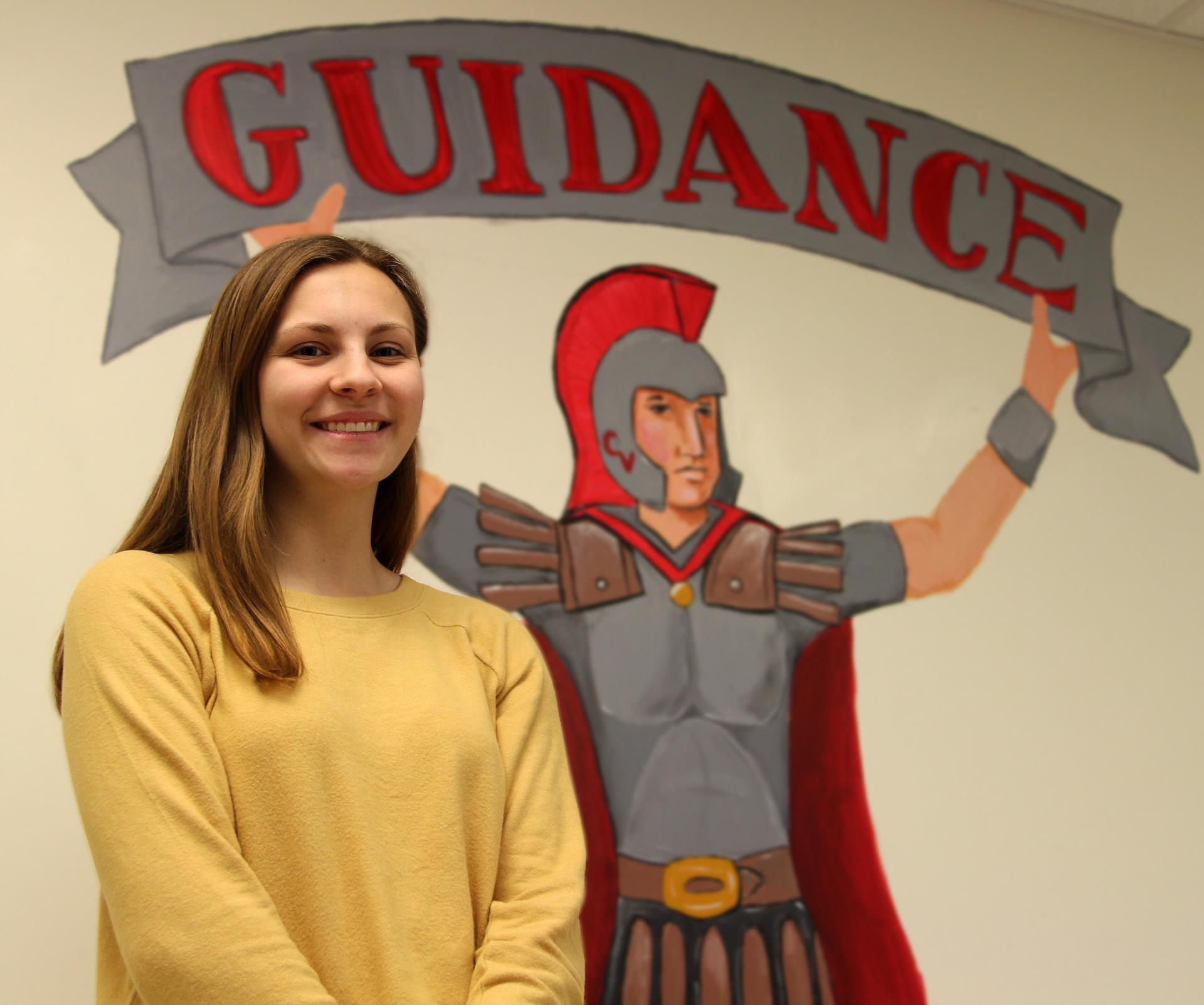 Katerina Retzlaff next to guidance sign