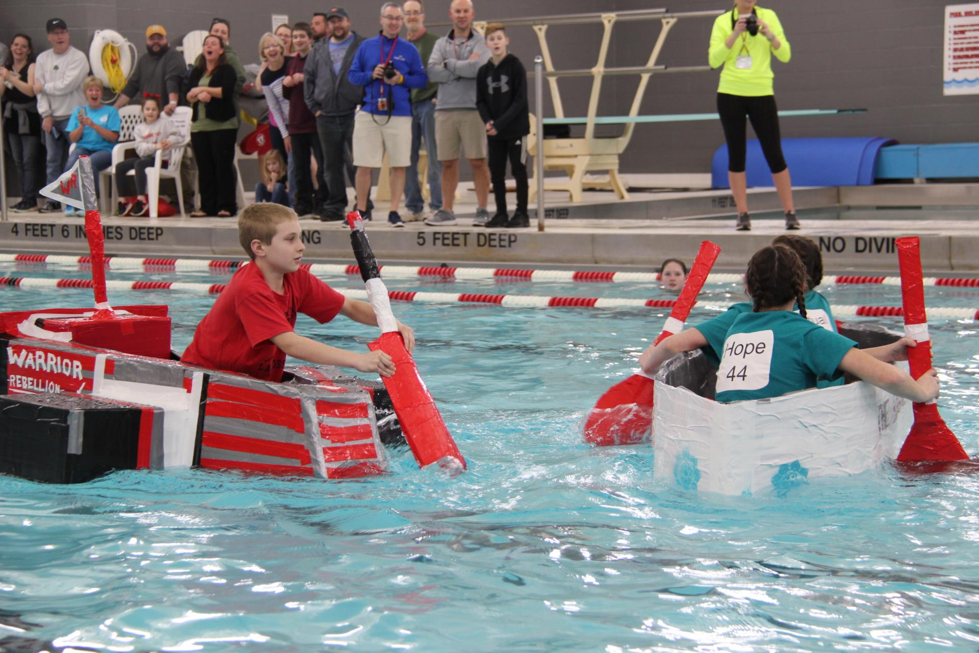 students racing cardboard boats in pool