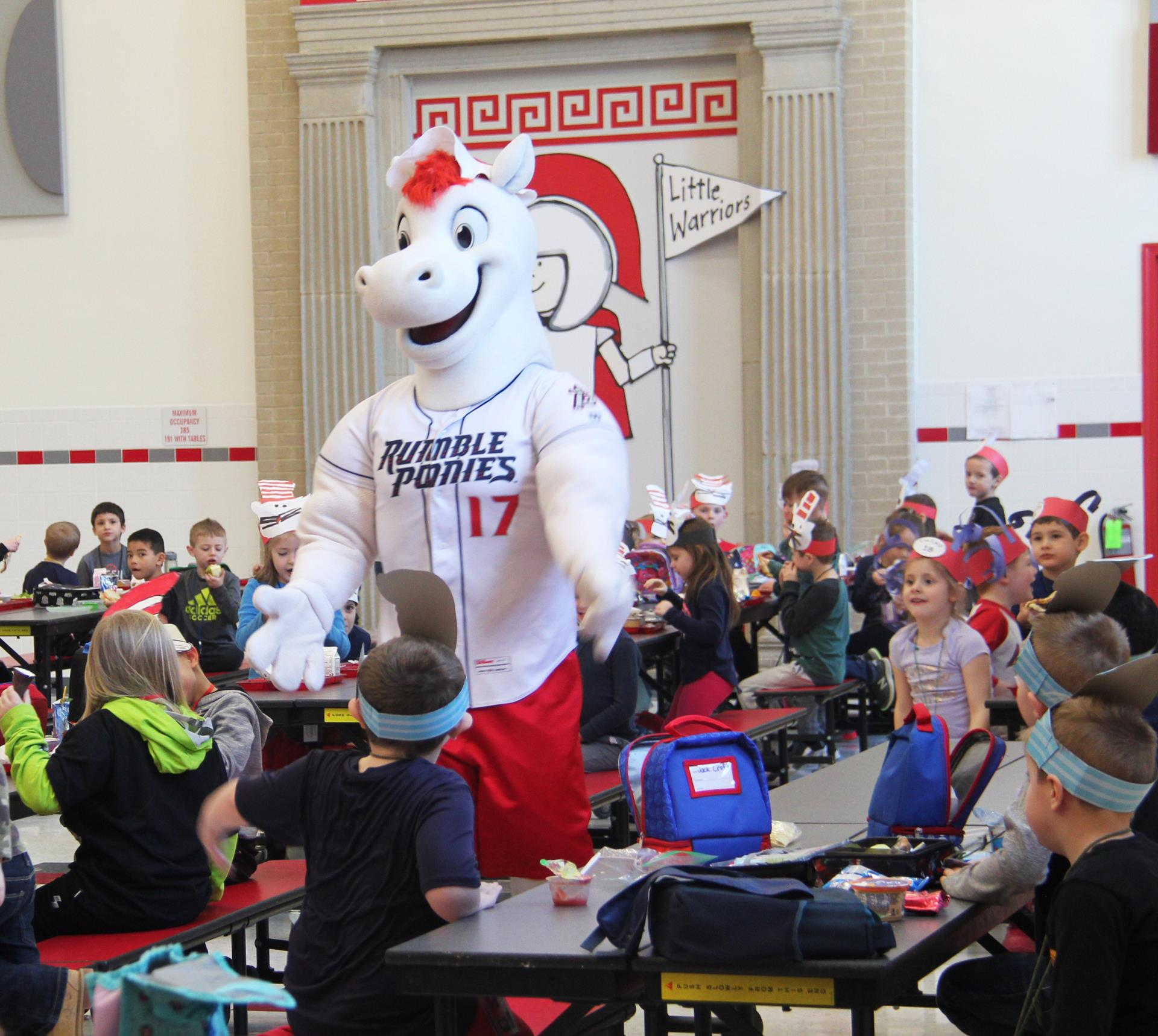 rowdy giving students high fives in cafeteria