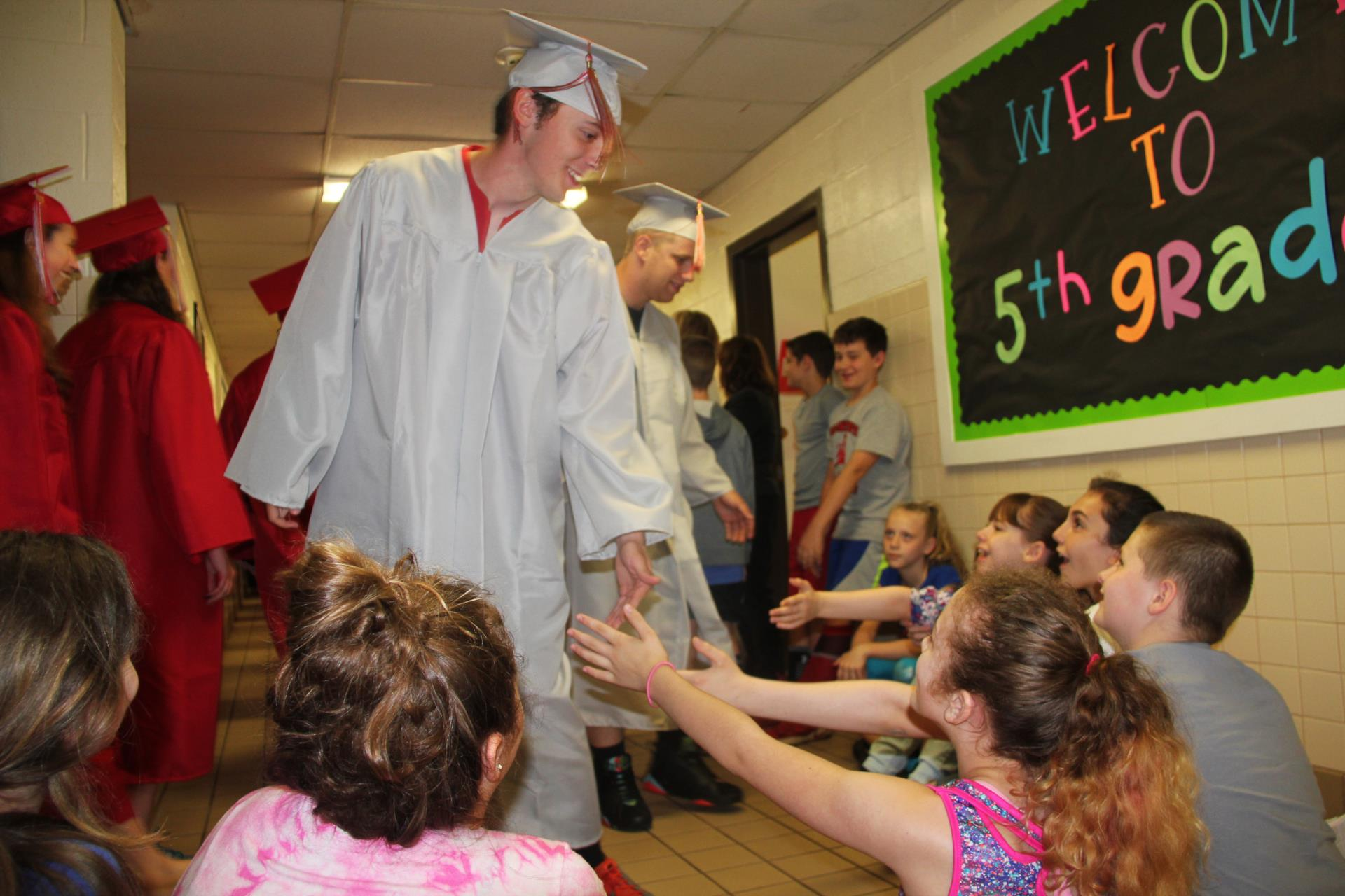 senior giving elementary students high fives