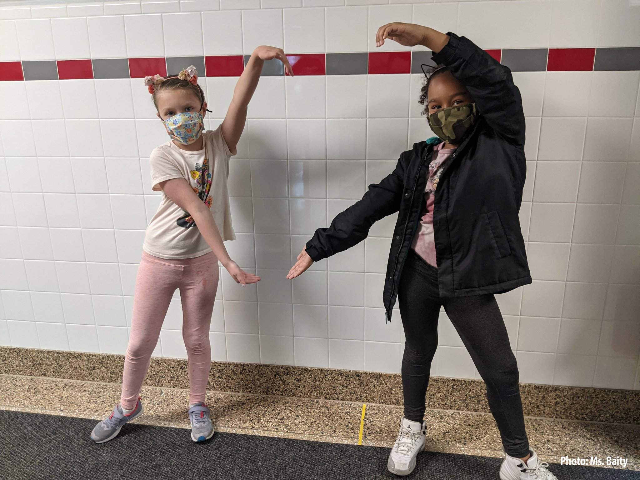 students dressed as cats making heart out of hands