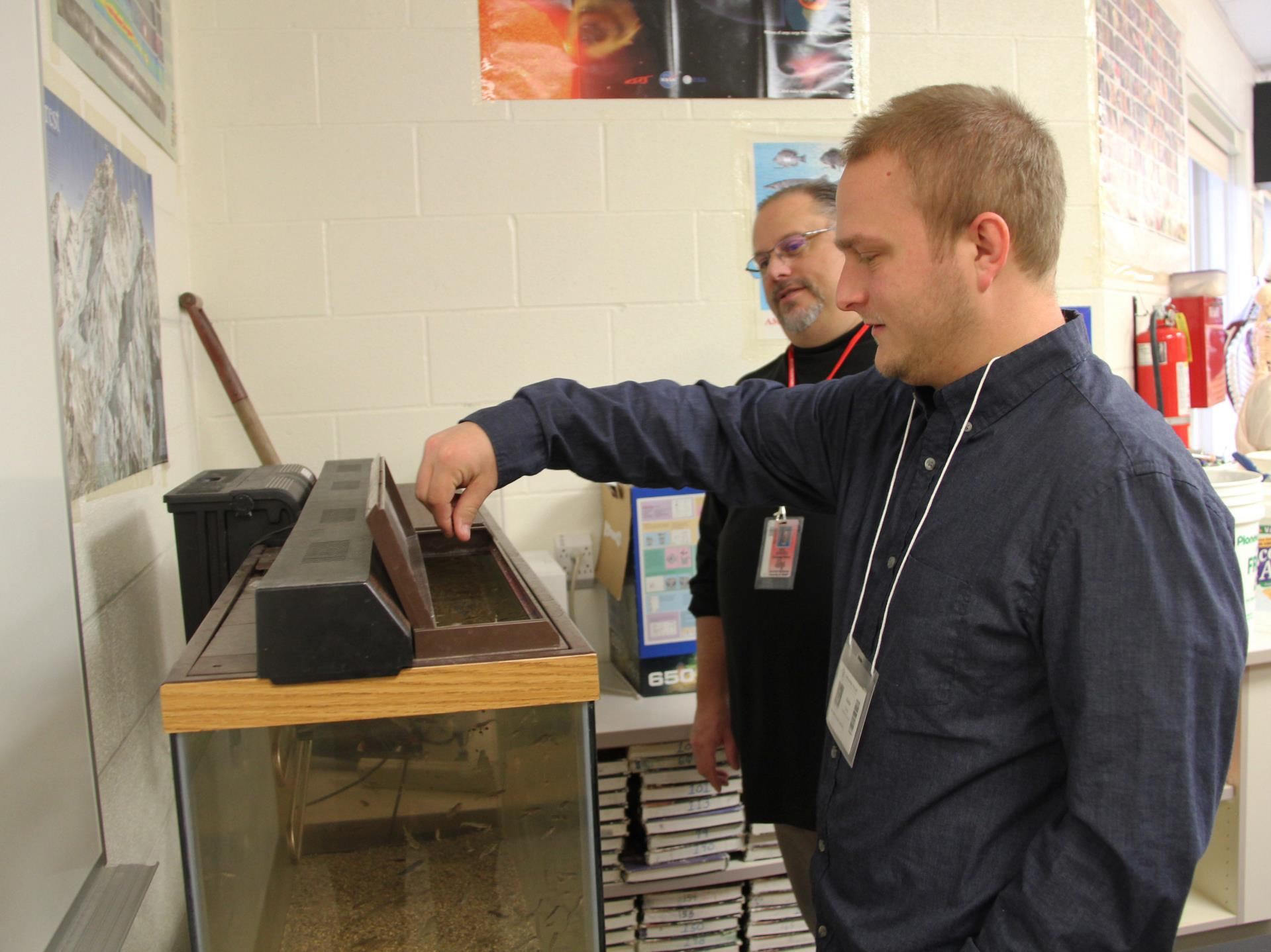 college student feeding fish with teacher