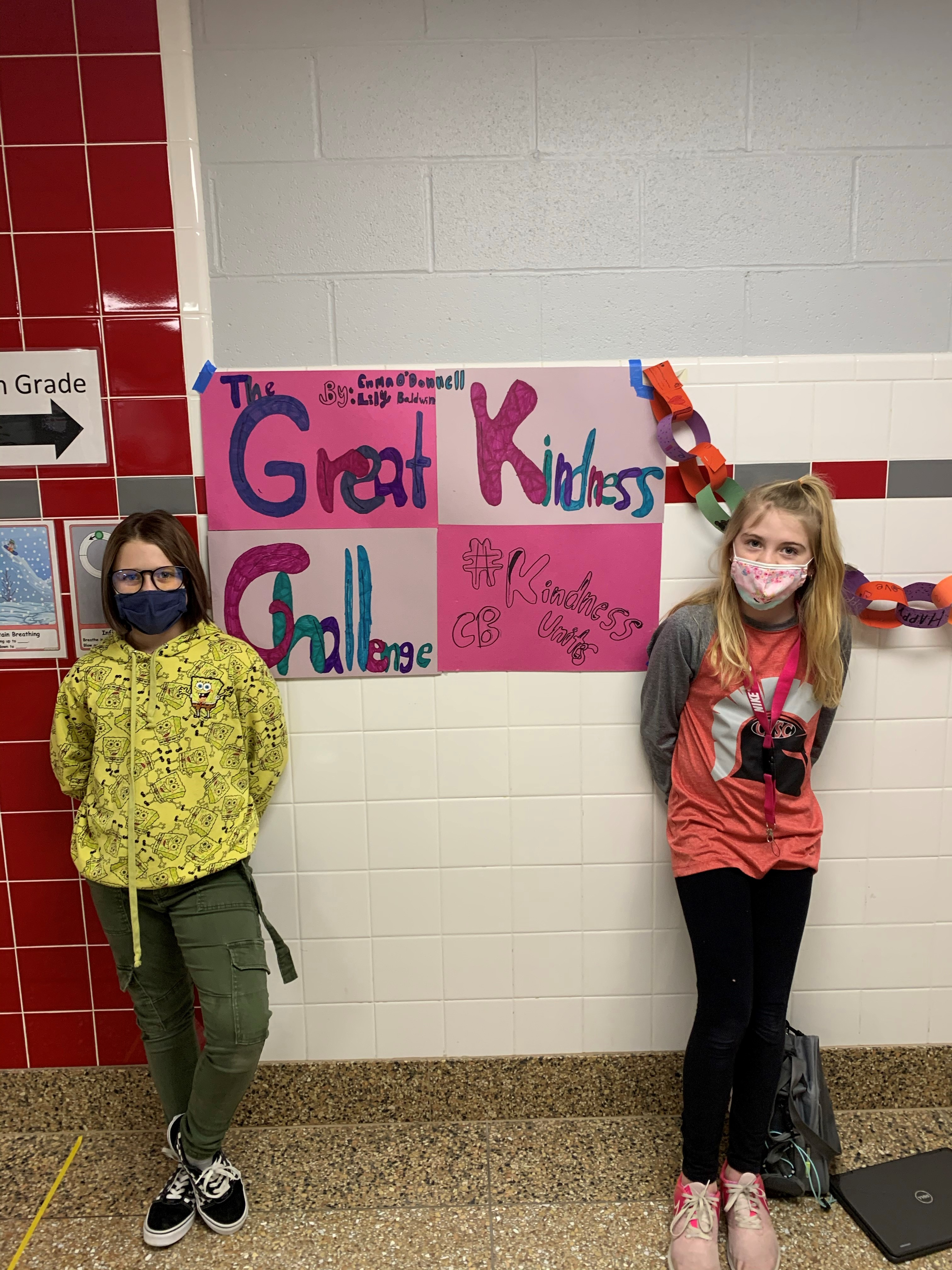 students standing next to great kindness challenge poster