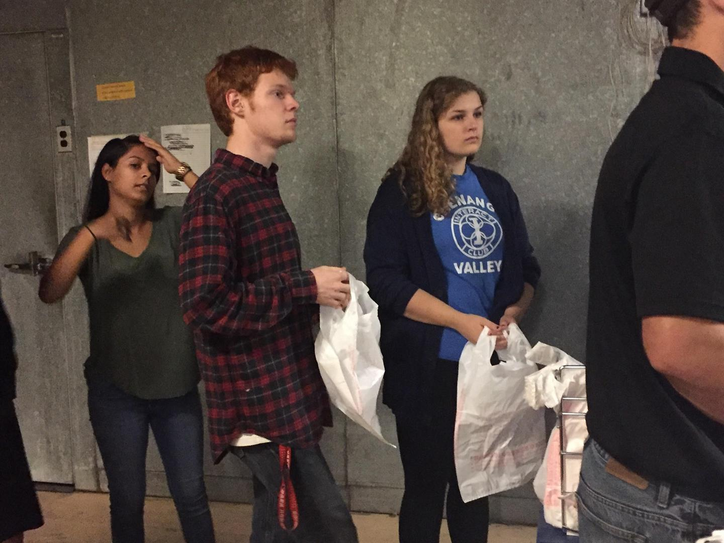 interact club officers peter jensen and mia hause stand in line to help fill bags for backpack program