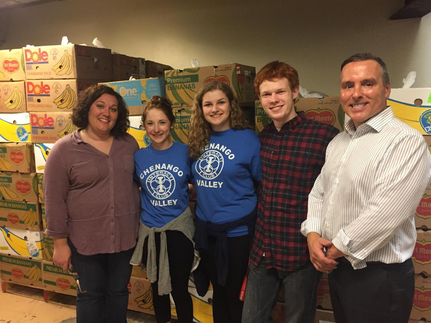 interact club officers smile in front of filled boxes with c v teacher anne marie griffin and superintendent david gill