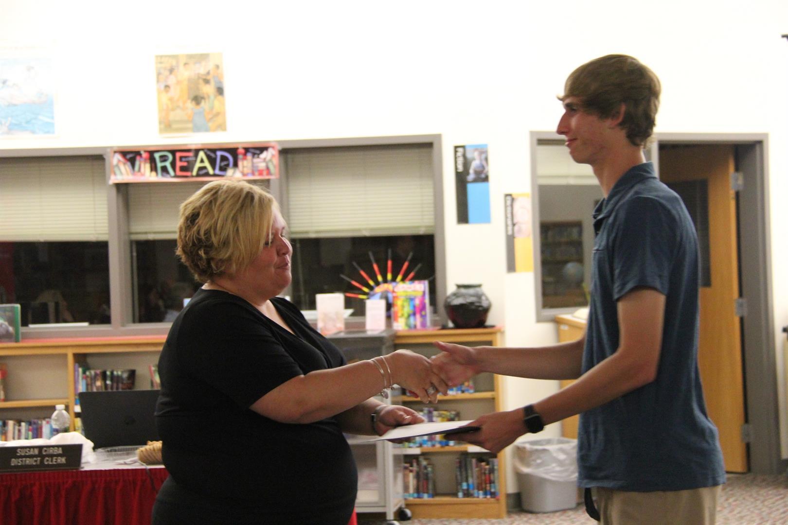 kelly warwick hands certificate to student craig salzman