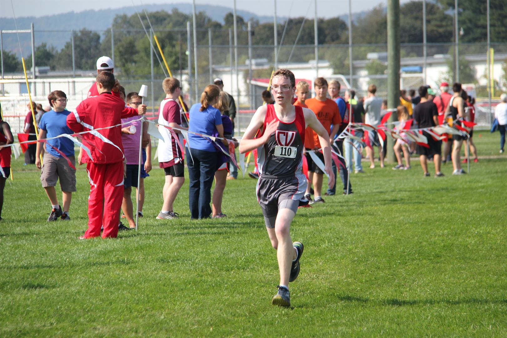 male student running at cross country meet