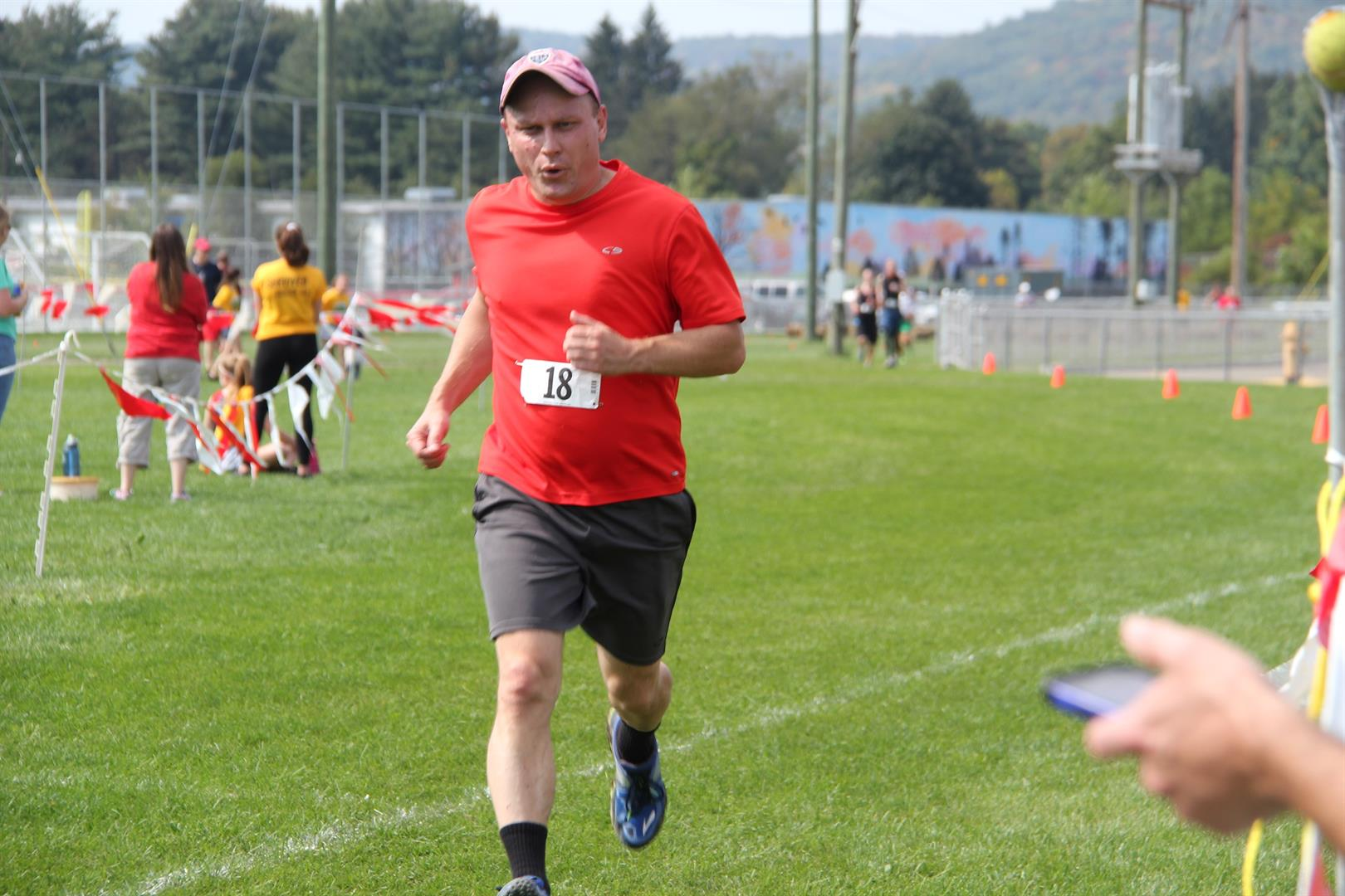 man running to finish line in cross country warrior challenge public 4 K