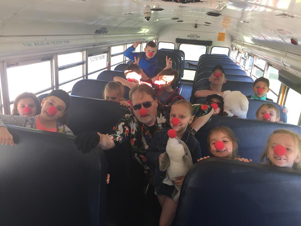 more students wearing red noses on bus