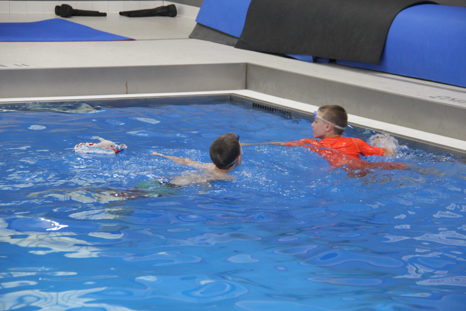 more students working on pool experiment with raft