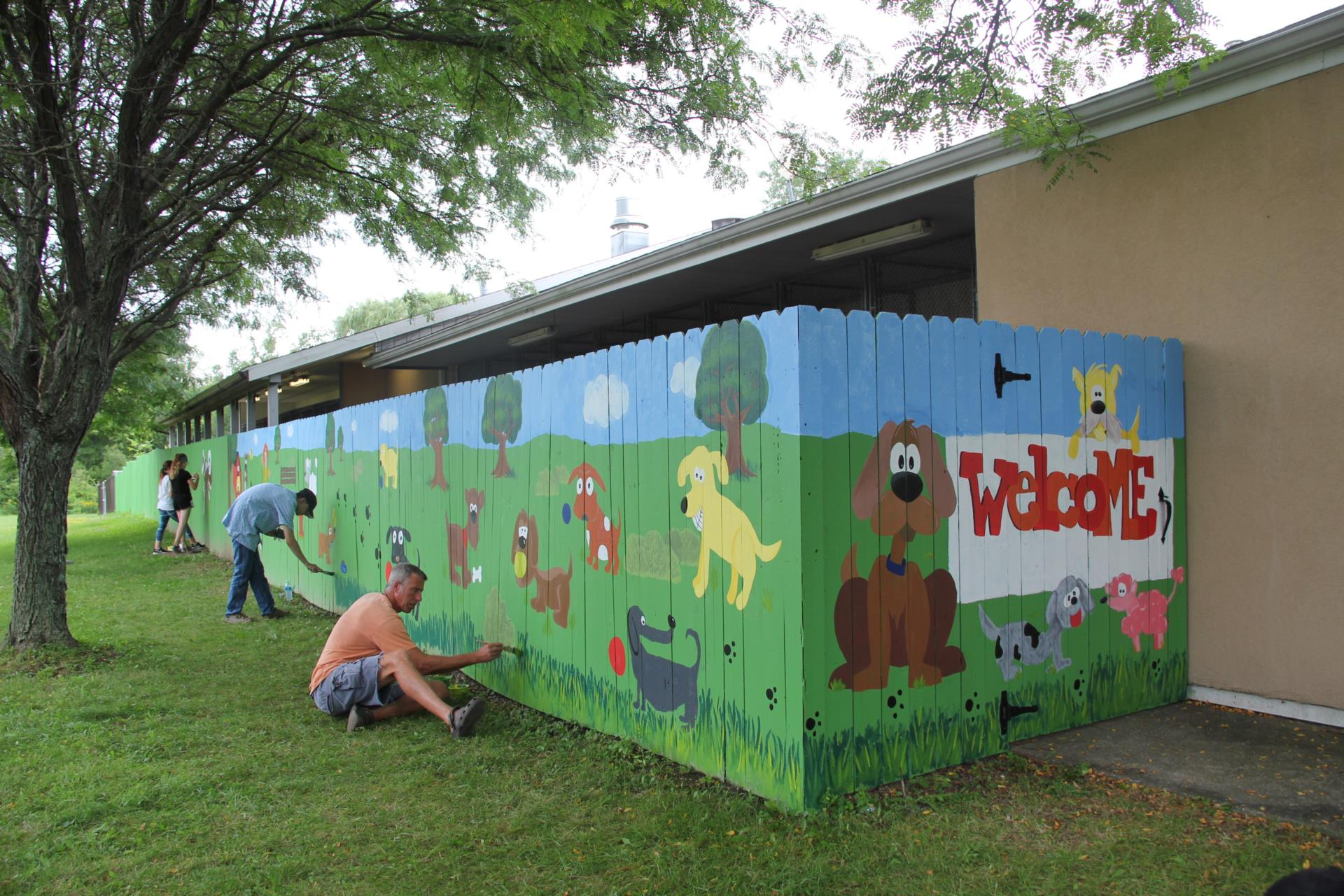 people working on mural at dog shelter