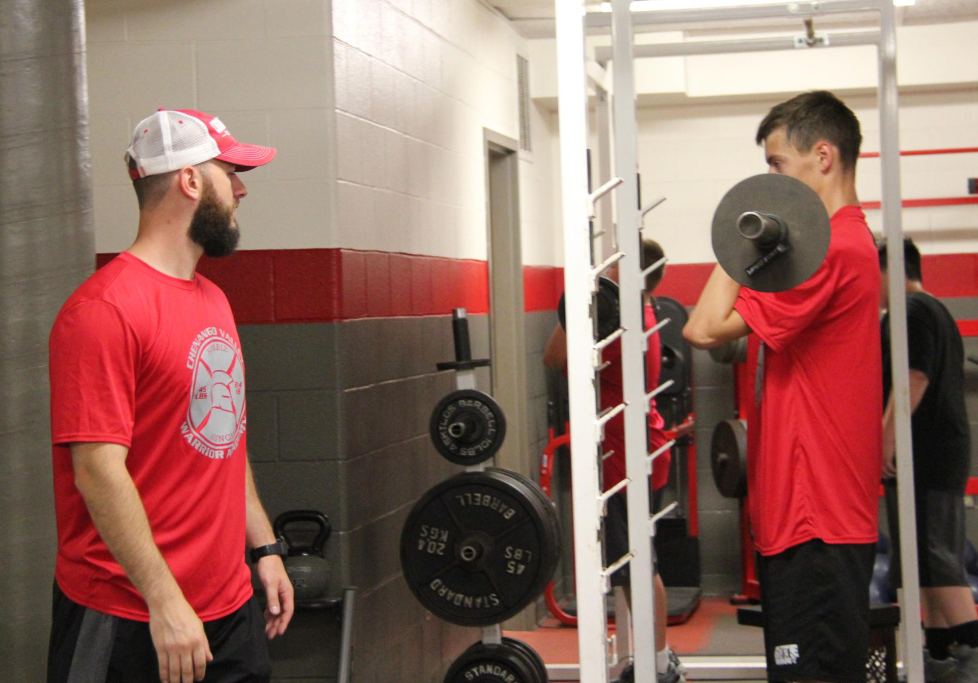 student lifting weight in warrior academy