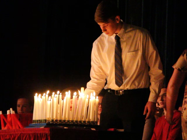 student lighting candles